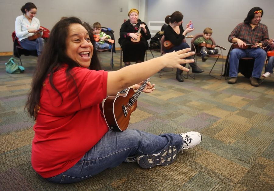 "Old Town School of Folk Music teacher Lanialoha Lee leads a class for children ages 3 to 5 learning to play the ukulele. The class was part of ""World Play Your 'Ukulele"" Day at the Vernon Area Public Library in Lincolnshire on Tuesday."