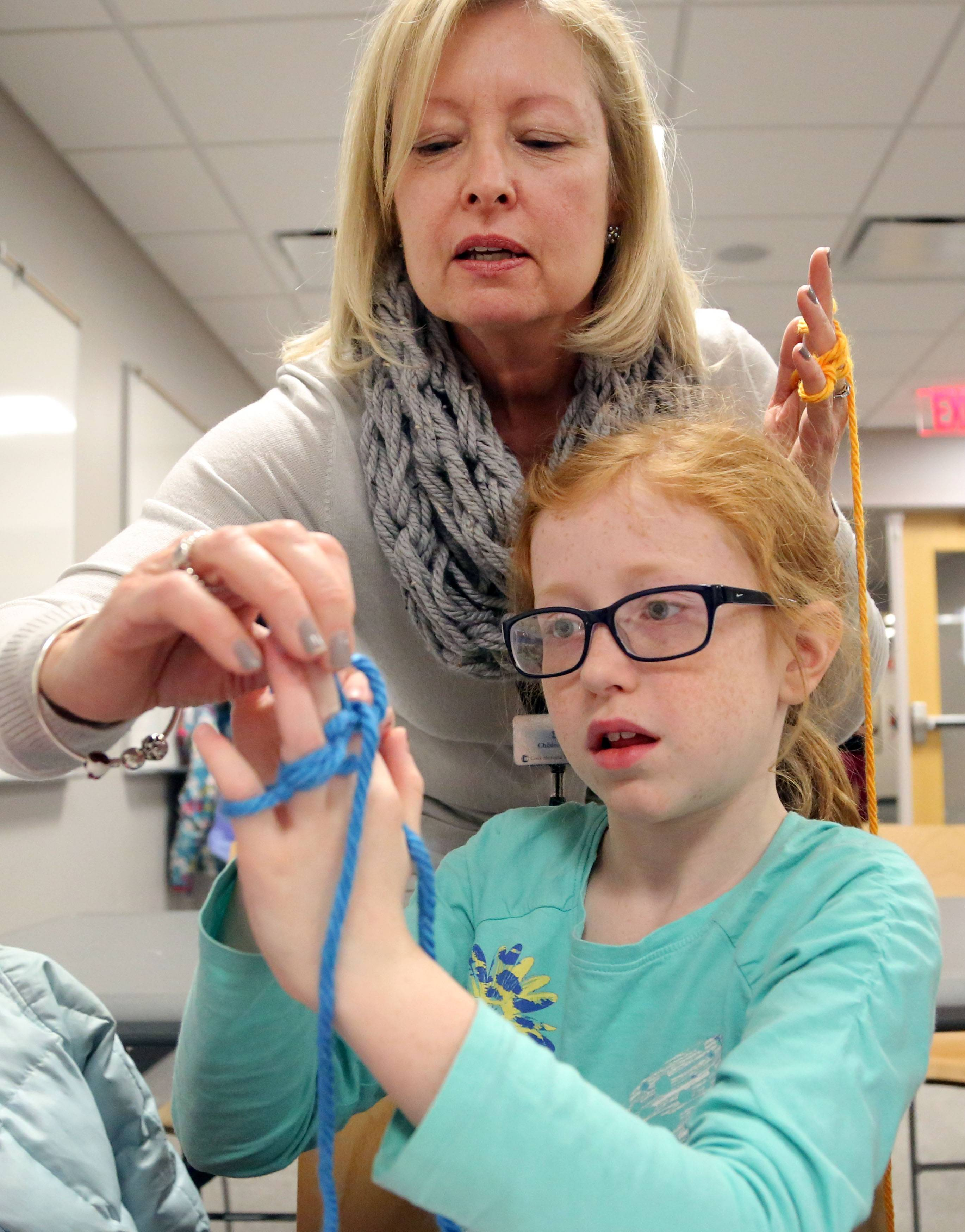 Children's Librarian Diana Trinkleback helps 9-year-old Madi Nelson of Libertyville as girls in grades 3-5 participated in a finger-knitting program at Cook Park Library in Libertyville.