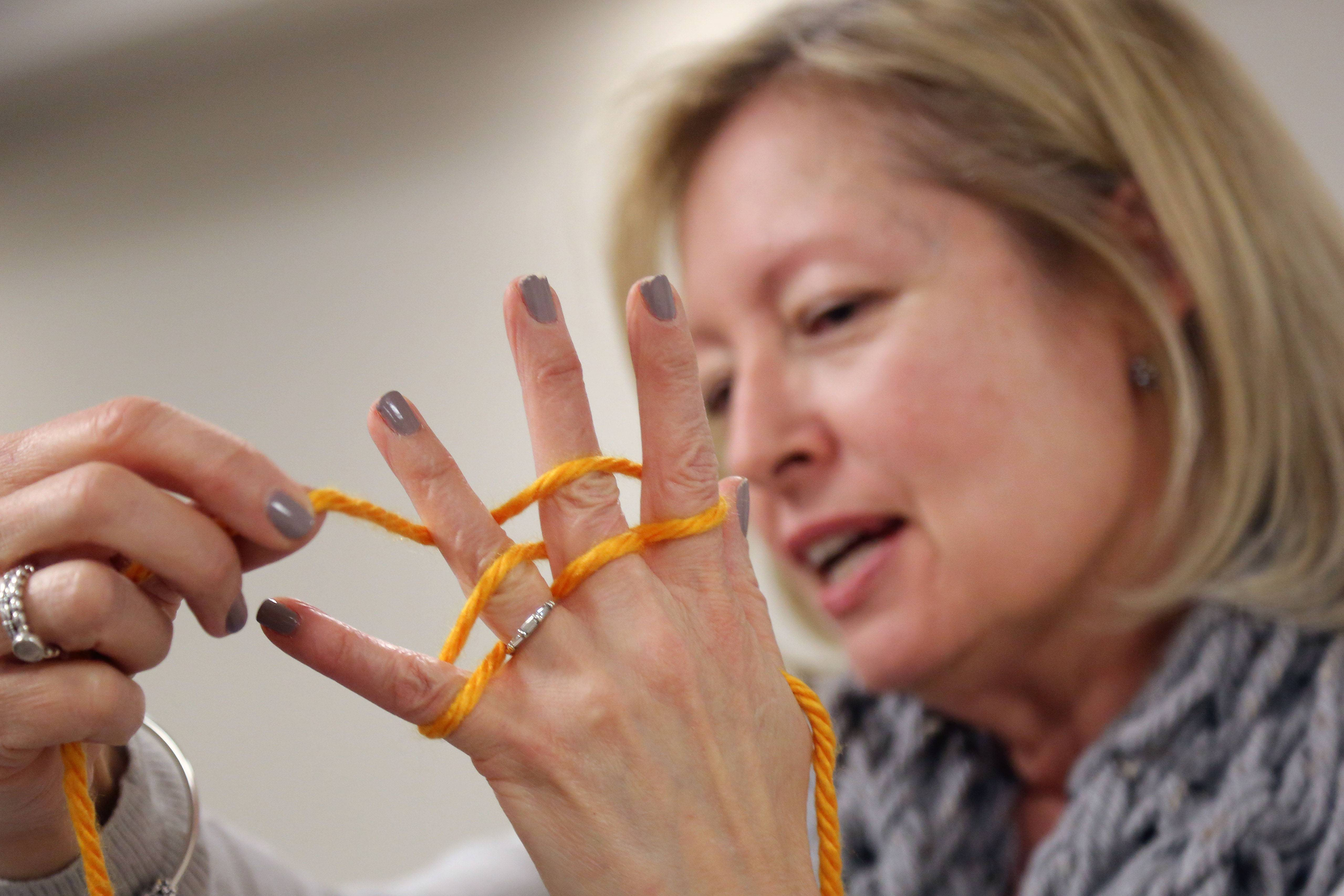 Children's Librarian Diana Trinkleback demonstrates a knitting technique using her fingers during a knitting program for kids in grades 3-5 at Cook Park Library.