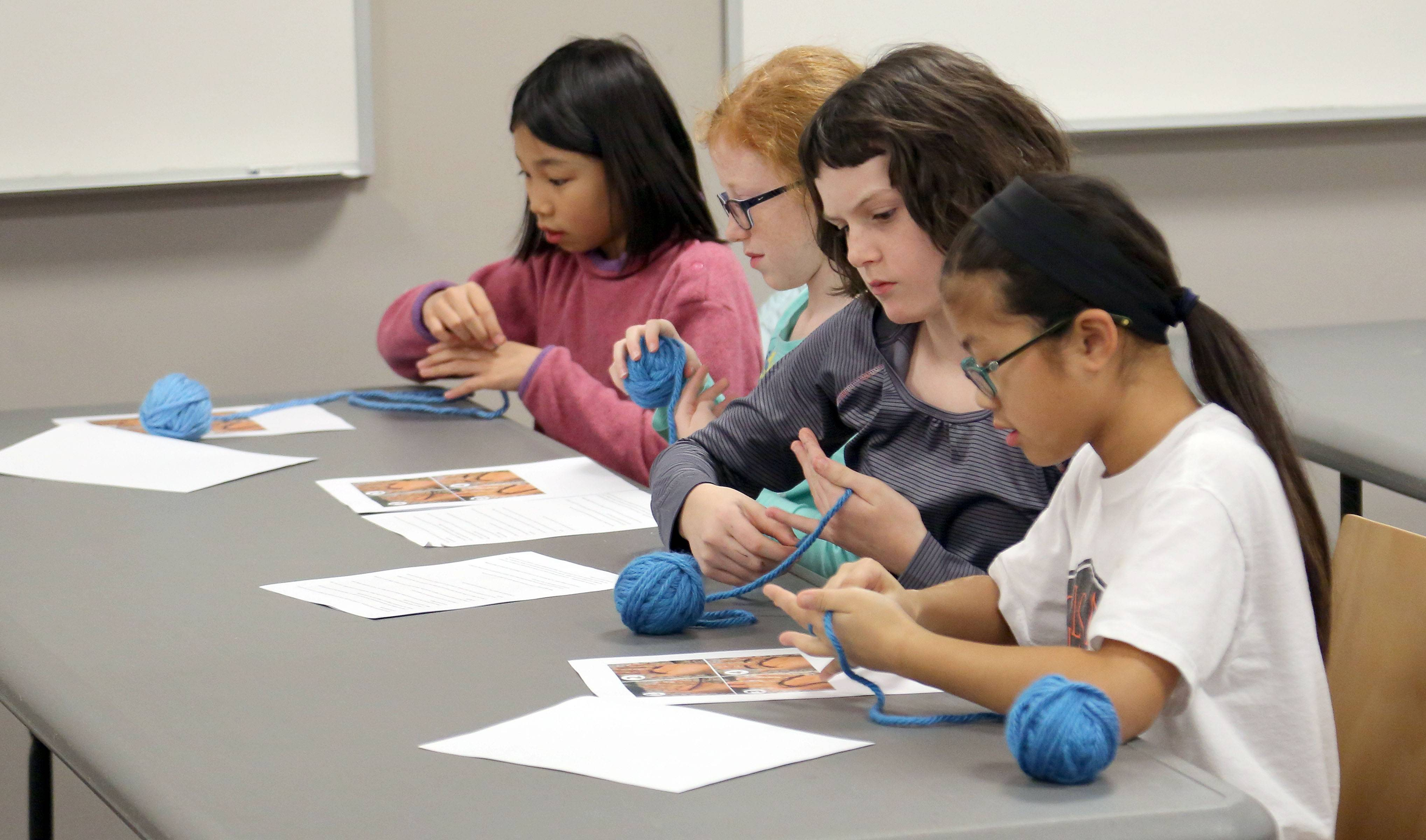 Girls experiment with yarn during a finger-knitting program at Cook Park Library.