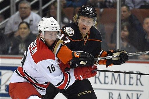 Carolina Hurricanes center Elias Lindholm, of Sweden, gets an elbow to the face from Anaheim Ducks defenseman Hampus Lindholm, of Sweden, during the second period of an NHL hockey game, Tuesday, Feb. 3, 2015, in Anaheim, Calif.