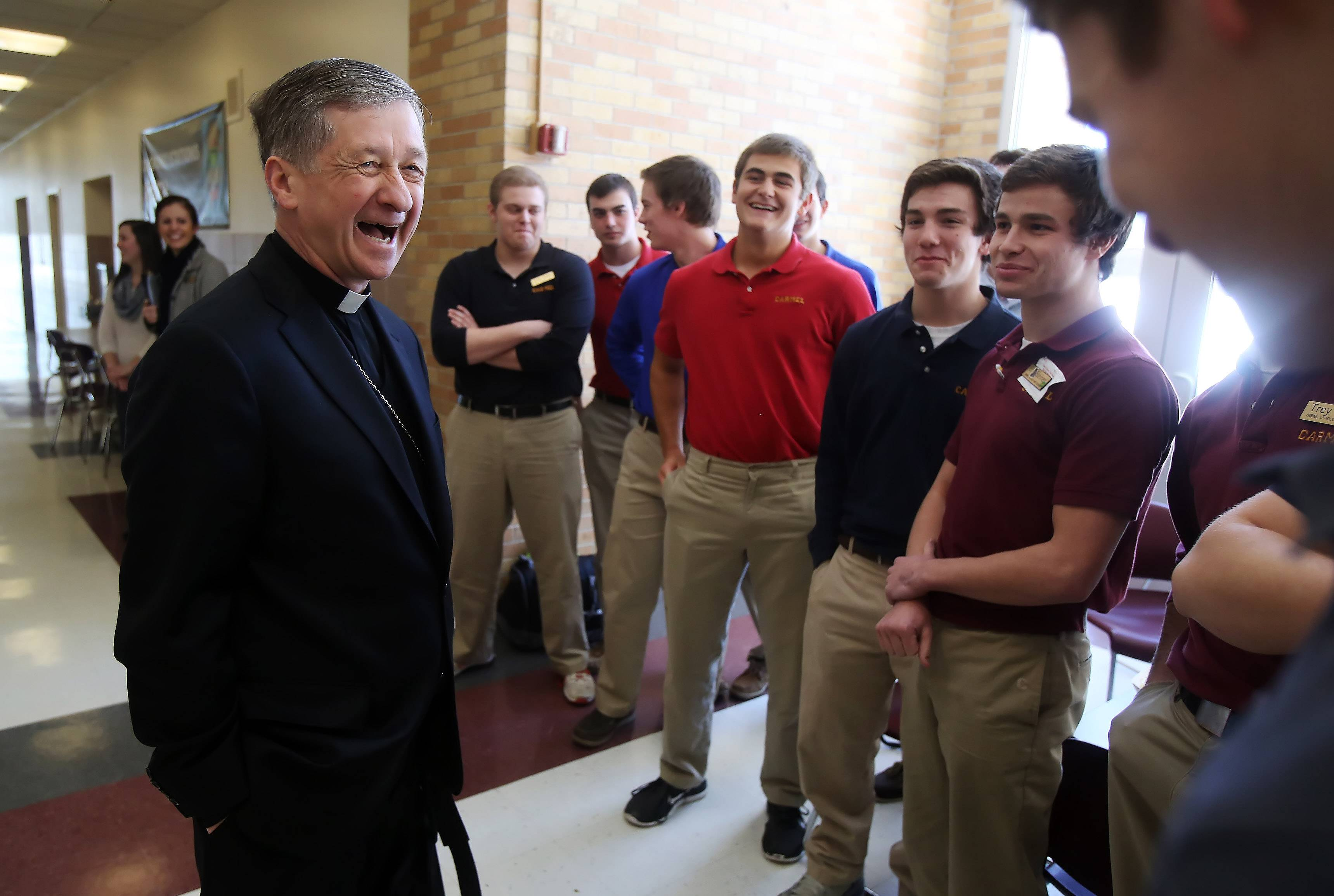 Chicago Archbishop Blase Cupich shares a laugh with several seniors during his tour of Carmel Catholic High School in Mundelein. Cupich stopped in classrooms, ate lunch with students and talked with teachers and employees during his hourlong visit Thursday.