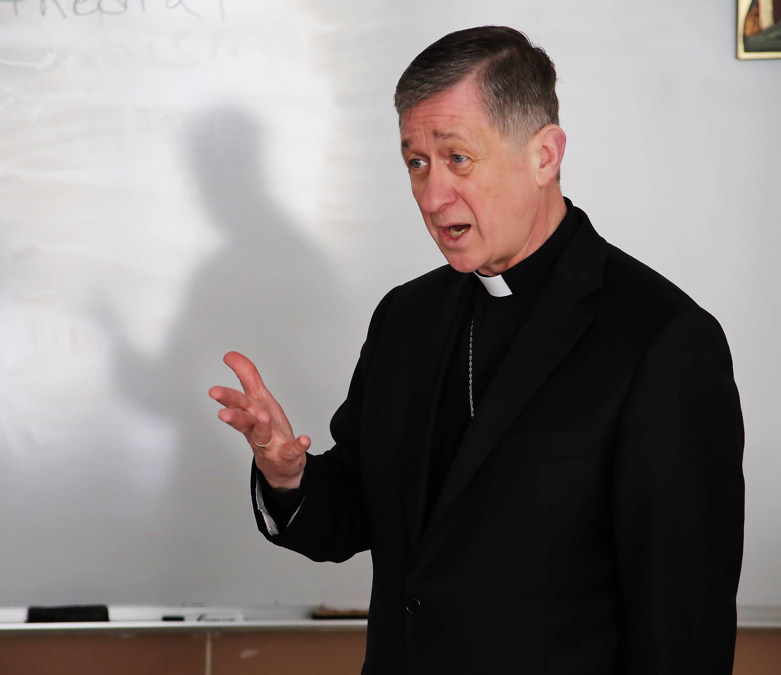 Chicago Archbishop Blase Cupich talks to Carmel Catholic High School religious studies students about gargoyles as part of his tour of the Mundelein school Thursday. Cupich stopped in classrooms, ate lunch with students and talked with teachers and employees during the hourlong visit.