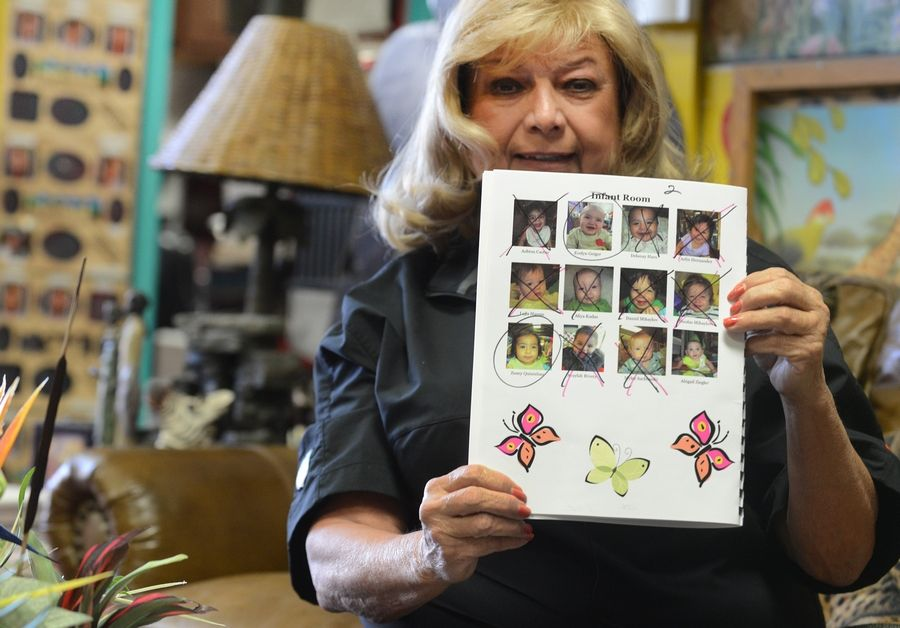 Robin Nordin, owner of Kiddie Junction Education Institute in Des Plaines shows a page out of the school's yearbook with faces crossed out of kids that will no longer be able to attend the school if the state can't afford to help pay for low-income parents' day care rates.