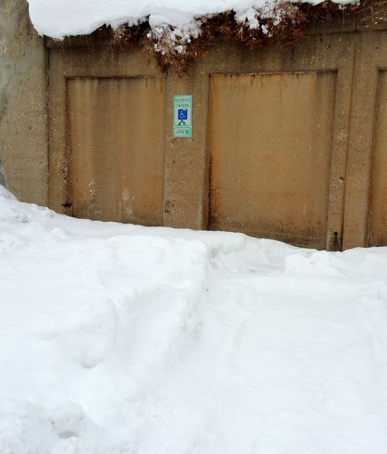 This parking spot reserved for people with disabilities remains buried in snow and ice. People who use wheelchairs face obstacles such as narrow pathways and snow mounds left by plows.