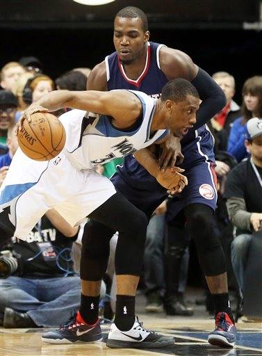 Minnesota Timberwolves' Thaddeus Young, left, drives around Atlanta Hawks' Paul Millsap in the first quarter of an NBA basketball game Monday, Feb. 9, 2015, in Minneapolis.