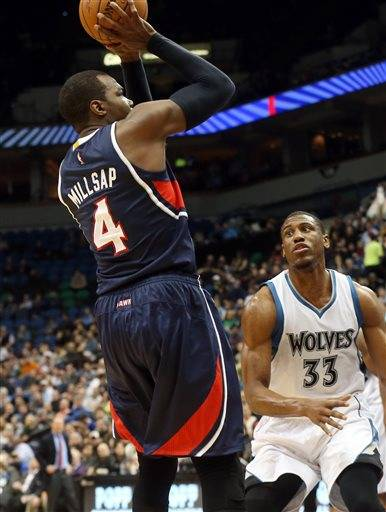 Atlanta Hawks' Paul Millsap, left, shoots as Minnesota Timberwolves' Thaddeus Young looks on in the first quarter of an NBA basketball game, Monday, Feb. 9, 2015, in Minneapolis.