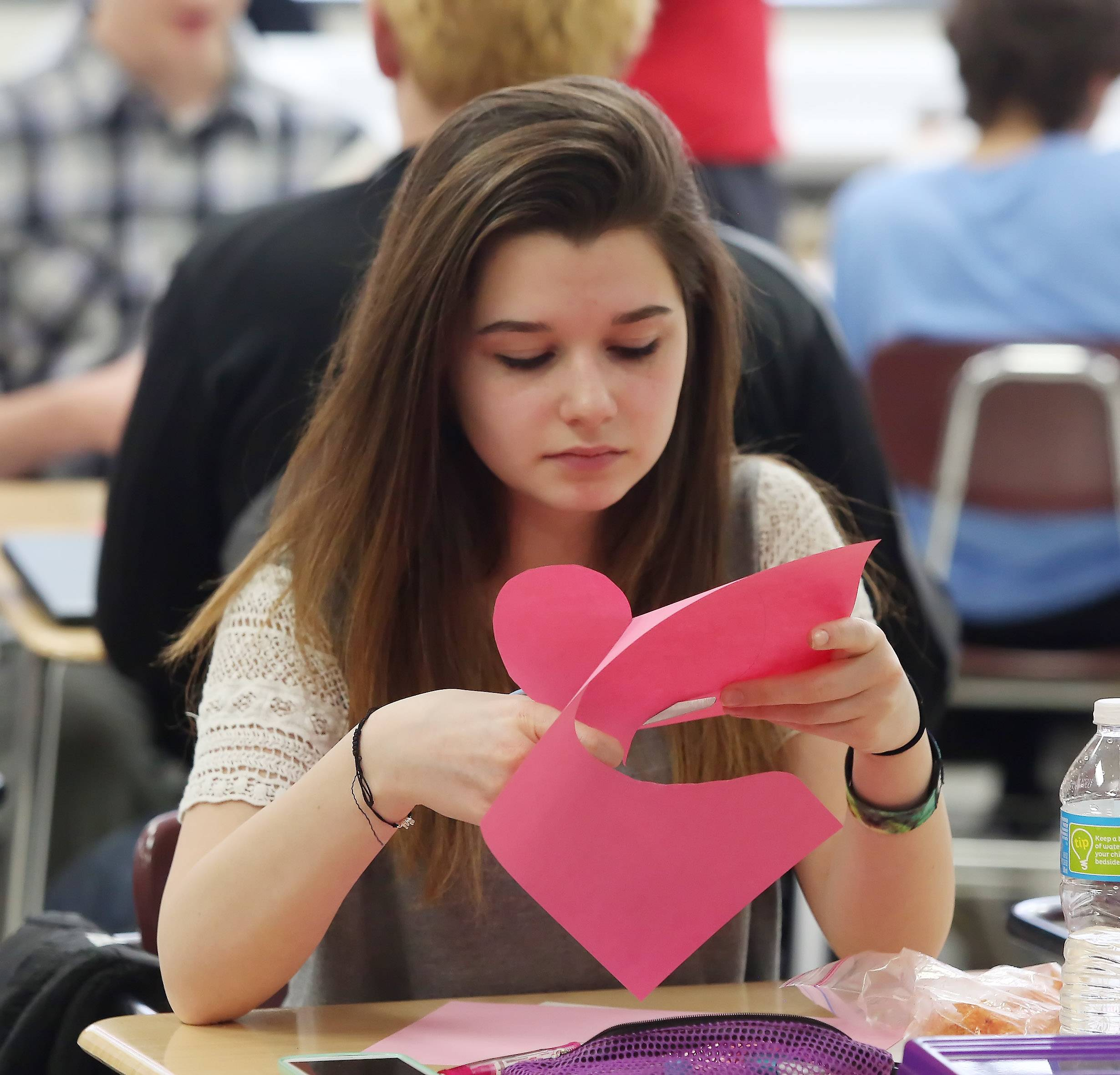 Freshman Maddie Martorana cuts out a heart as she and fellow Mundelein High School students made Valentine's Day cards Wednesday for Spanish-speaking veterans. The school's Spanish classes are working with Midwest Veteran's Closet to distribute the cards.