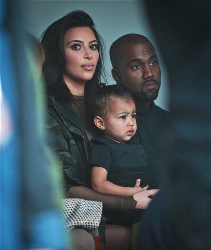 3794ac30a98af Kim Kardashian and Kanye West sit with their daughter North West during a  rehearsal for the