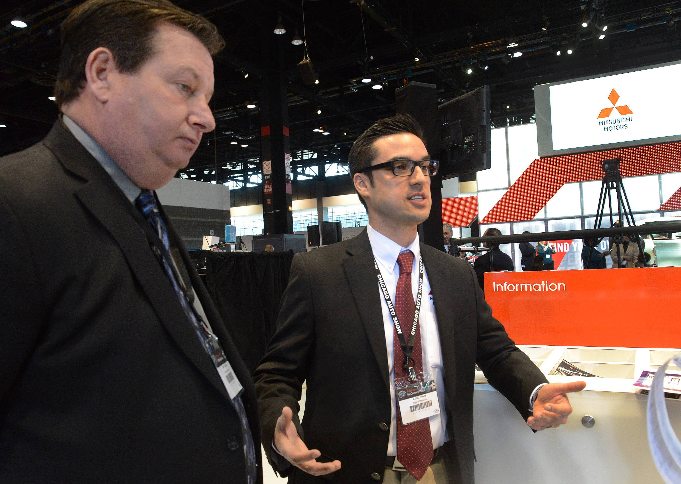 Thomas Hughes of Schaumburg Mitsubishi, left, and Emal Noor of Biggers Mitsubishi in Elgin talk about the new Mitsubishi offerings at the 2015 Chicago Auto Show.