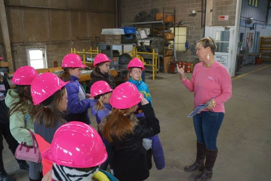 "Louisa McCarthy, CFO of Walt, LTD, gives a tour of the company's DeKalb tool and machine factory to youngsters in Northern Illinois University's new STEM Divas program, aimed at keeping ""girly-girls"" interested in science. The program launches in April at the NIU Naperville campus."