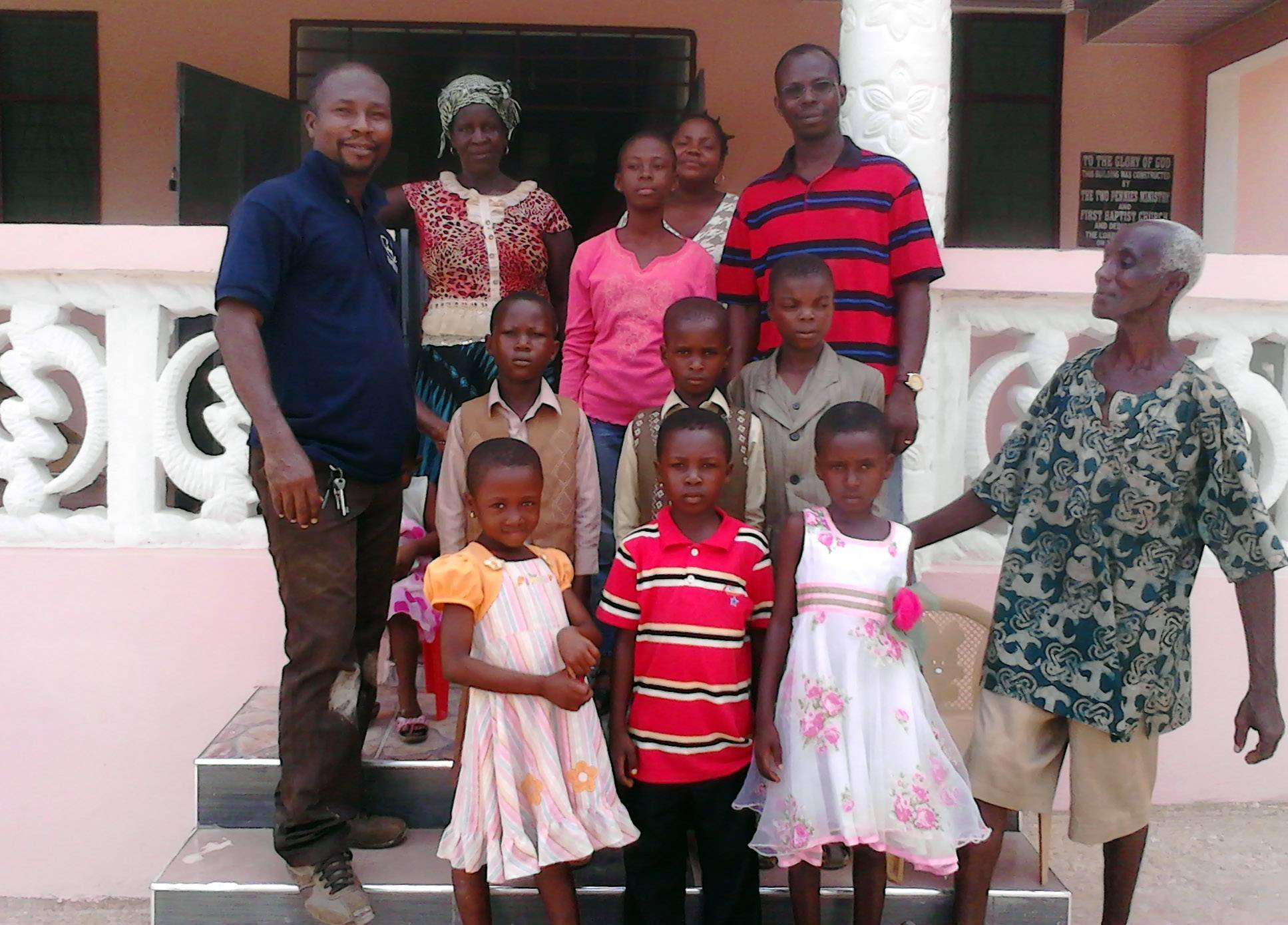 Aboagye Kwesi Prah, left, the Two Pennies Ghanaian representative, is pictured with some of the children at the newly built orphanage in Ghana. On the upper right is Ebenezer, the founder of the home.