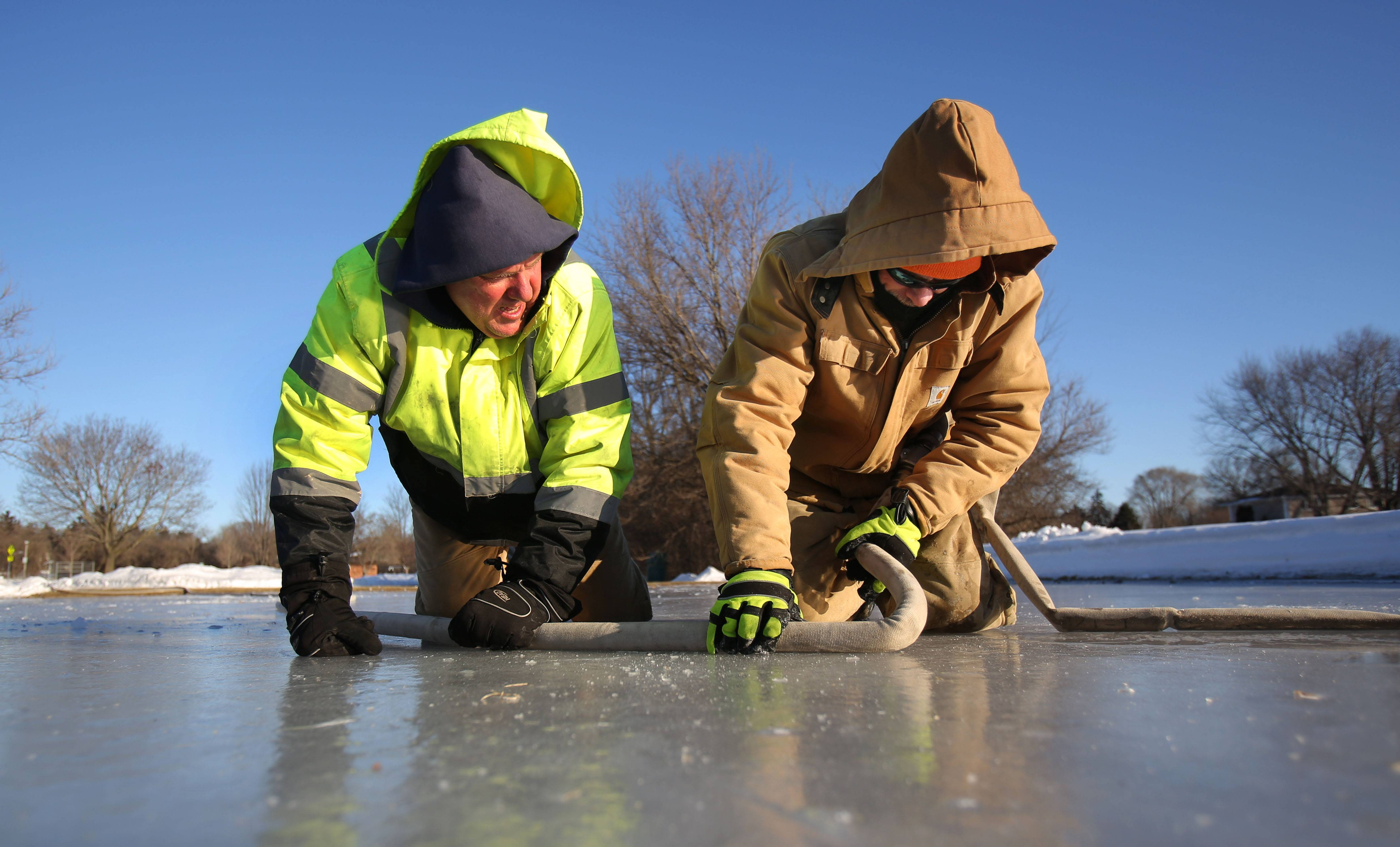 Libertyville Public Works employees Jeff Panella, left, and Victor Bobadilla, try to soften a frozen section of hose as they work on freezing the ice rink at Nicholas-Dowden Park, as temperatures dipped into the single digits Thursday in Libertyville.