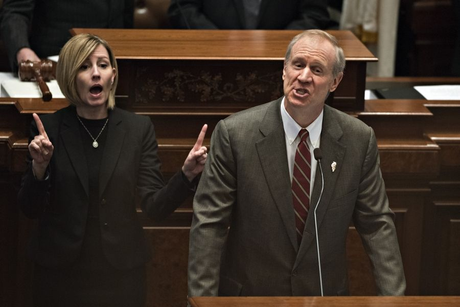 A sign language interpreter, left, works next to Bruce Rauner, governor of Illinois, as he delivers a budget address in the House Chamber of the State Capitol building in Springfield. Rauner proposed spending cuts across state programs from Medicaid to universities to stanch the fiscal bleeding in Illinois, the nation's worst-rated state.