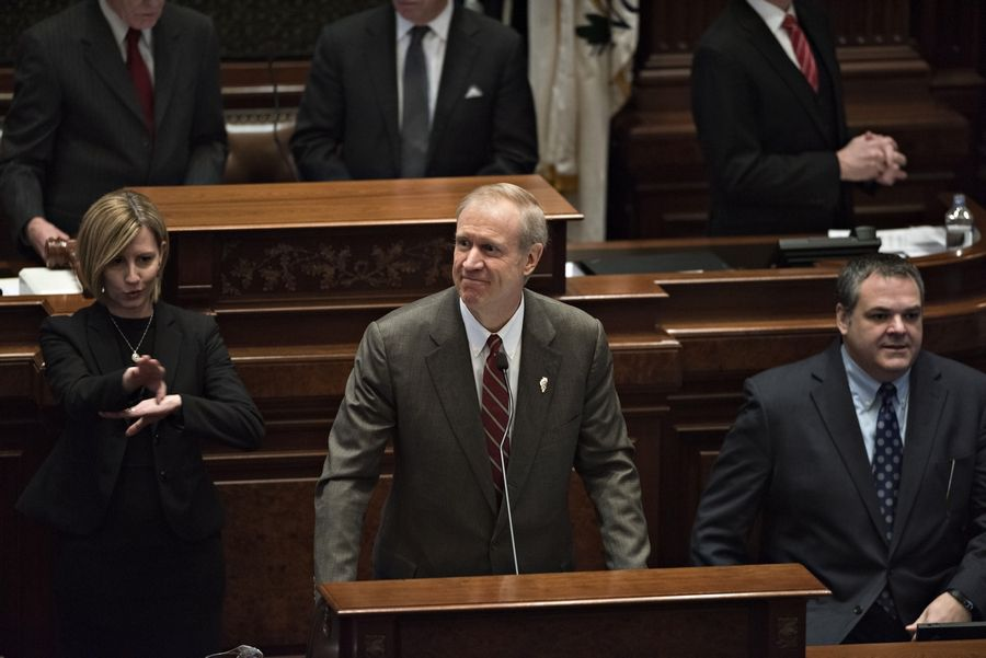 A sign language interpreter, left, works next to Bruce Rauner, governor of Illinois, as he delivers his budget address. Rauner proposed spending cuts across state programs from Medicaid to universities to stanch the fiscal bleeding in Illinois, the nation's worst-rated state.