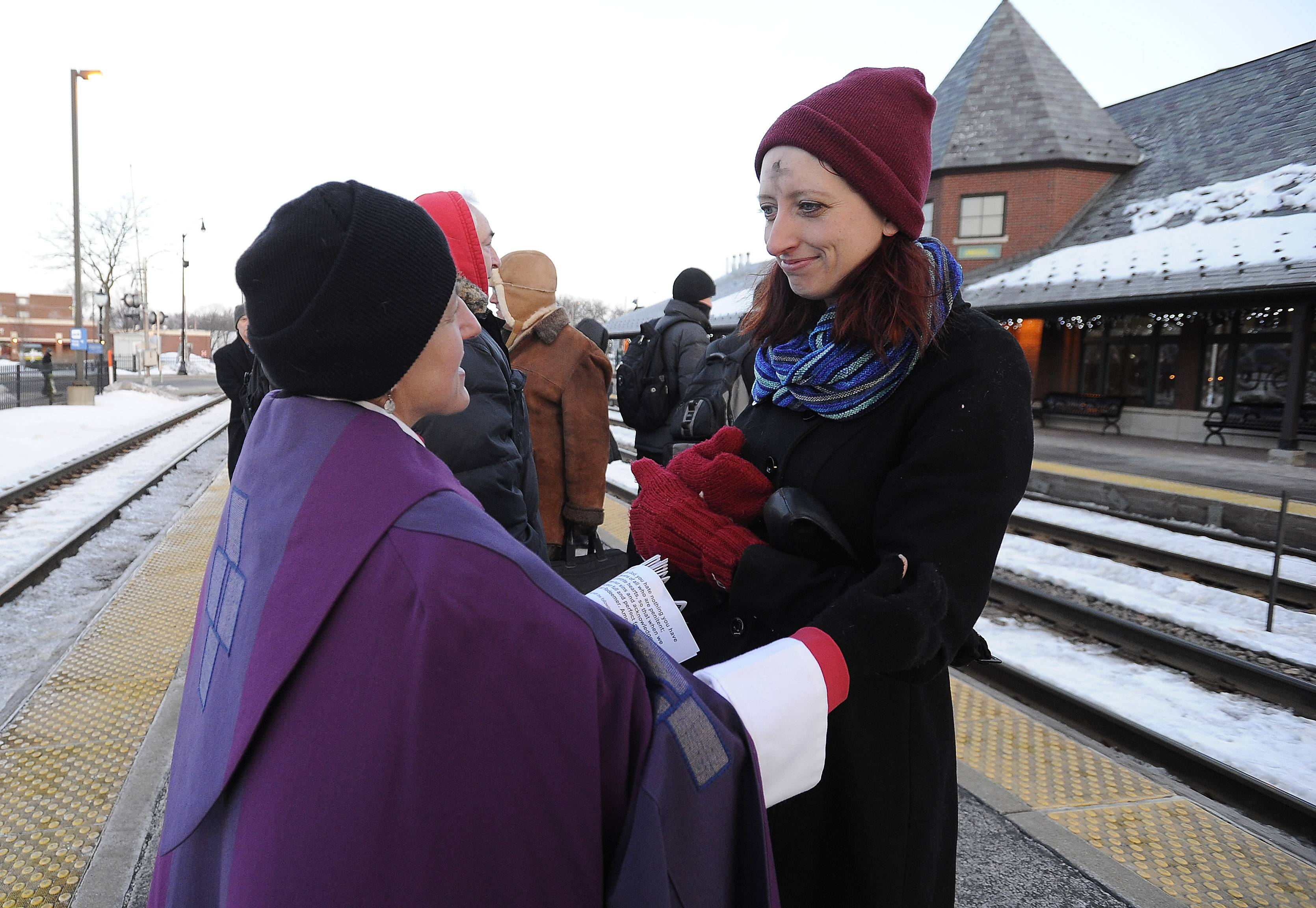 The Rev. Elizabeth Butler Jameson of St. Simon's Episcopal Church in Arlington Heights gives ashes to commuter Bridget Jeffrief of Palatine at the Arlington Heights train station on Ash Wednesday.