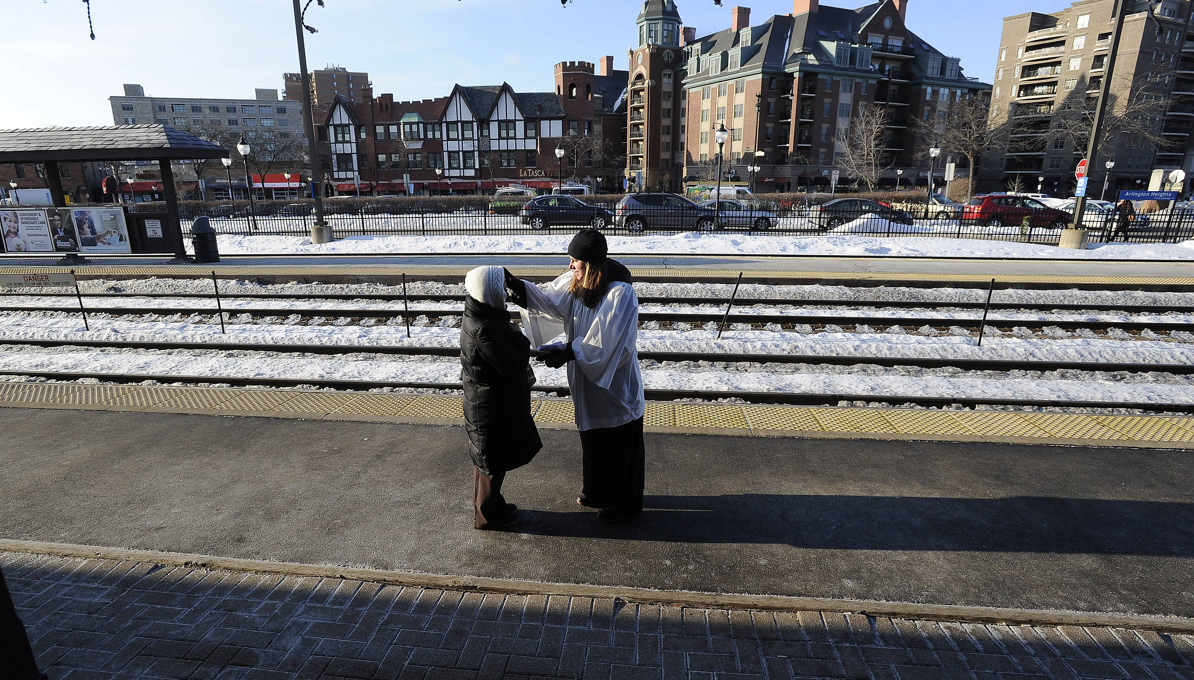 Beth Carter, 28, a member of St. Simon's Episcopal Church in Arlington Heights, gives ashes to a commuter Wednesday at the Arlington Heights Metra station.