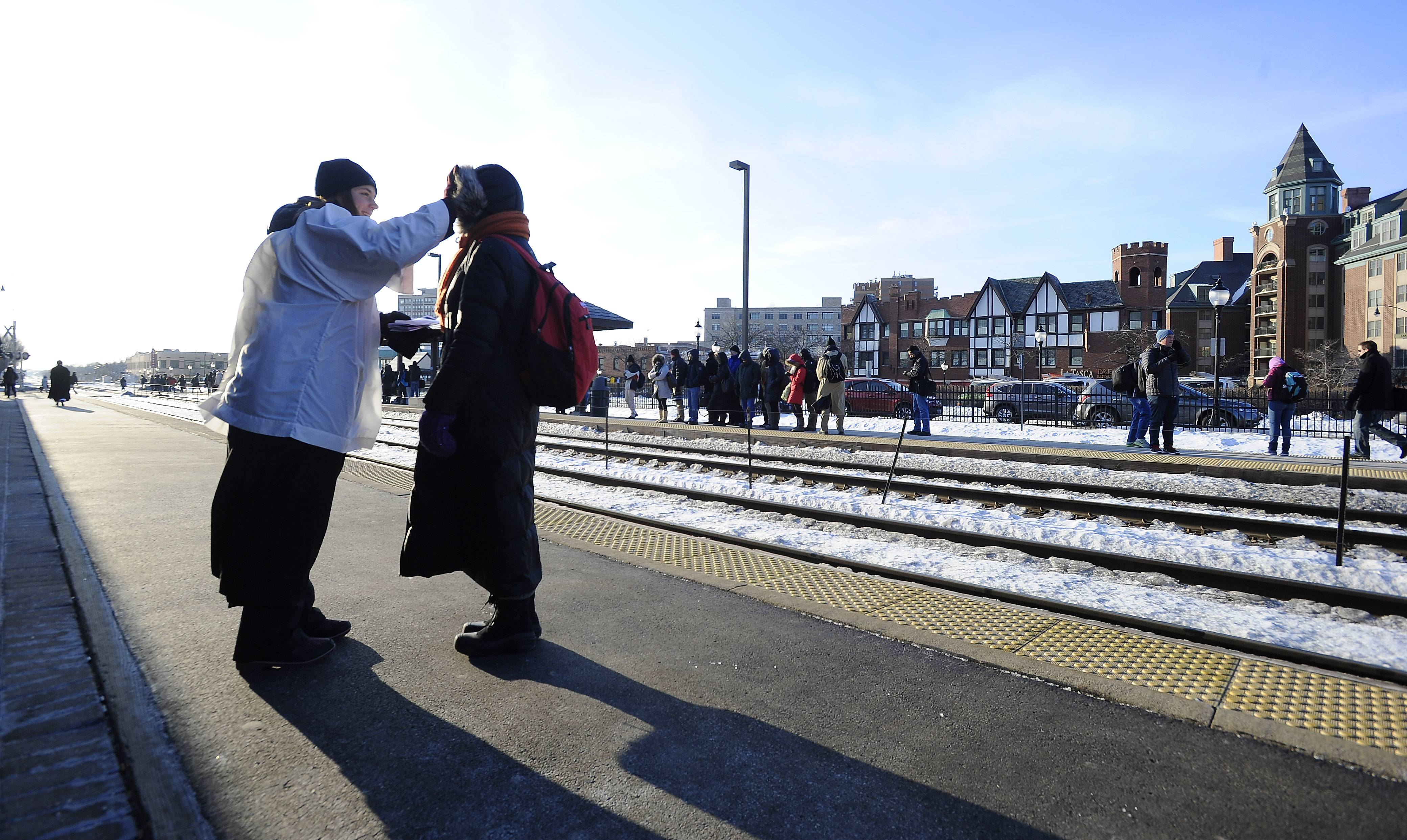 Beth Carter, 28, a member of St. Simon's Episcopal Church in Arlington Heights, gives ashes to Elizabeth Eich of Arlington Heights at the Metra station on Ash Wednesday.
