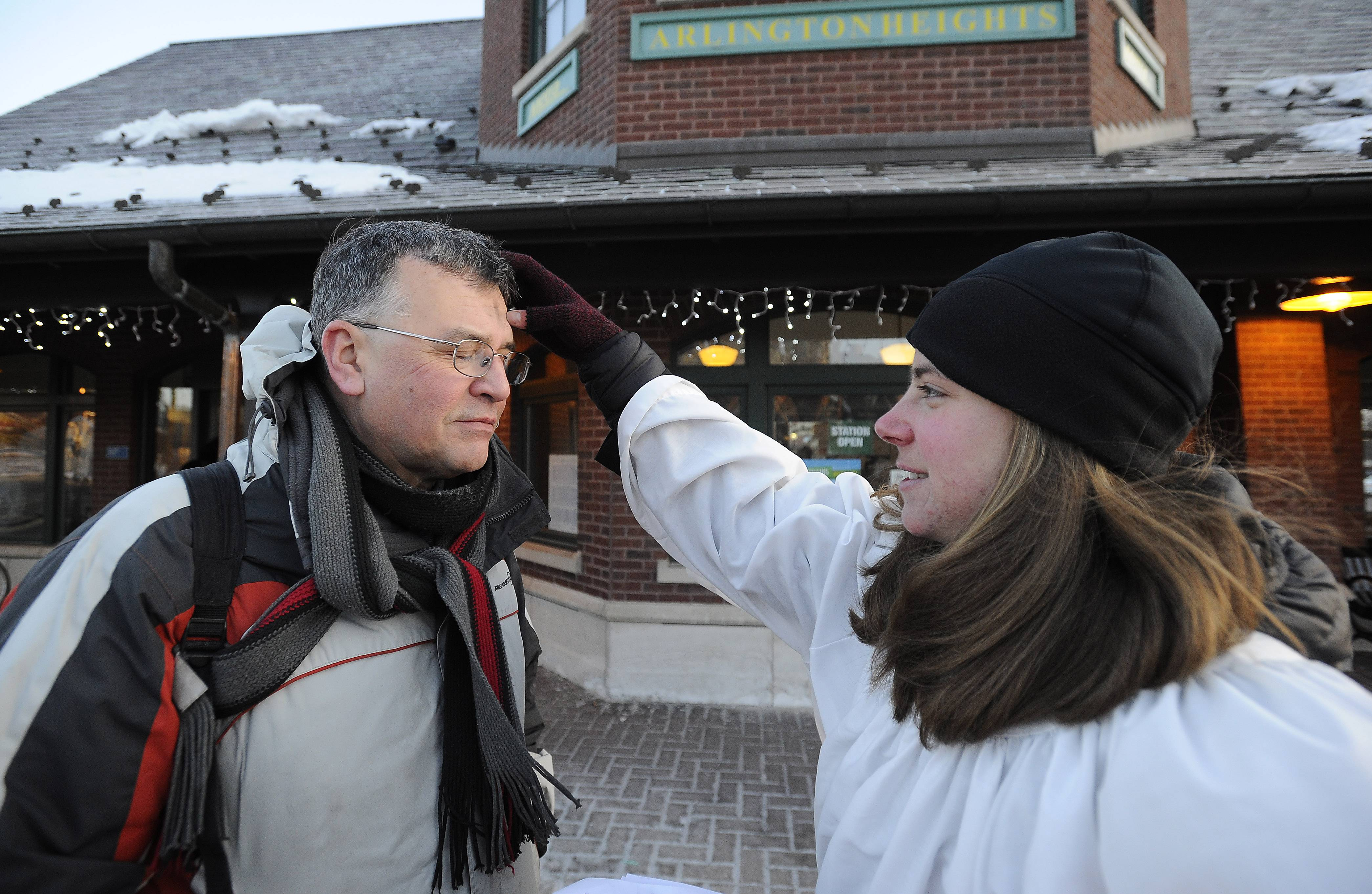 Beth Carter, 28, a member of St. Simon's Episcopal Church in Arlington Heights, gives ashes to Bob Rebl of Elk Grove Village at the Arlington Heights Metra station on Ash Wednesday.
