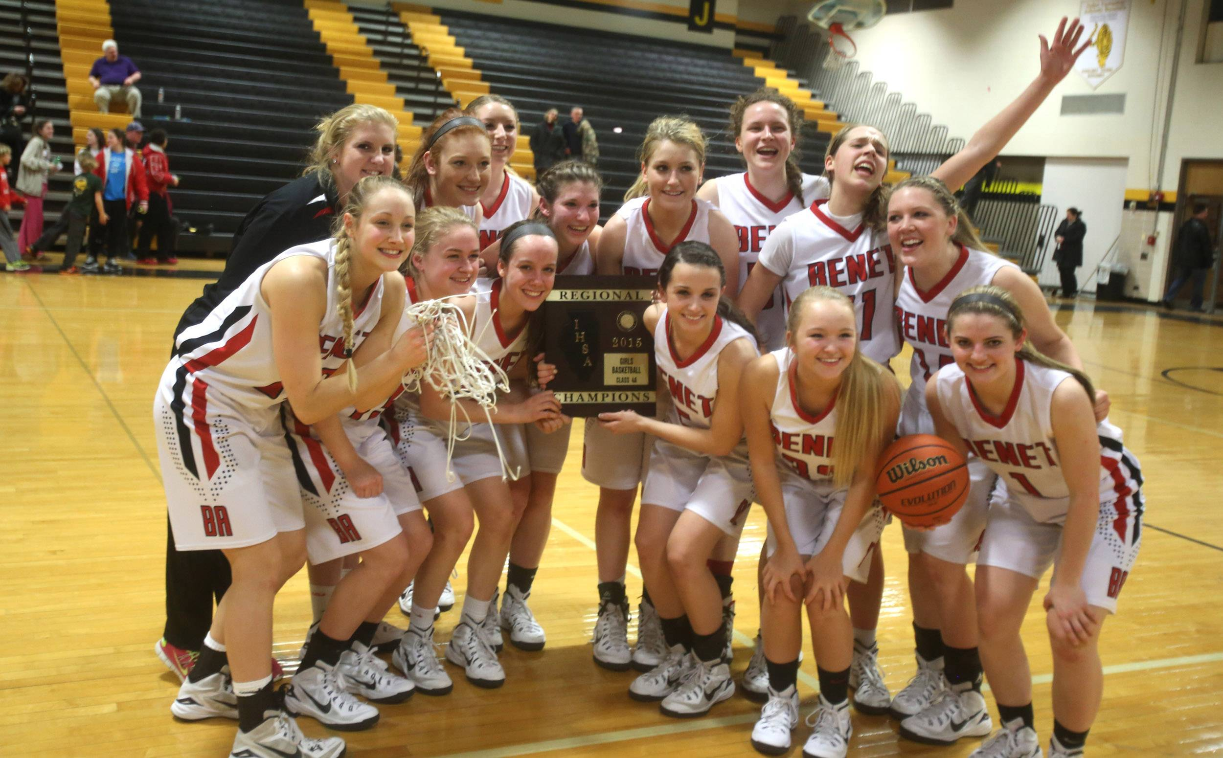 Benet players celebrate after winning the Joliet West regional girls basketball championship.