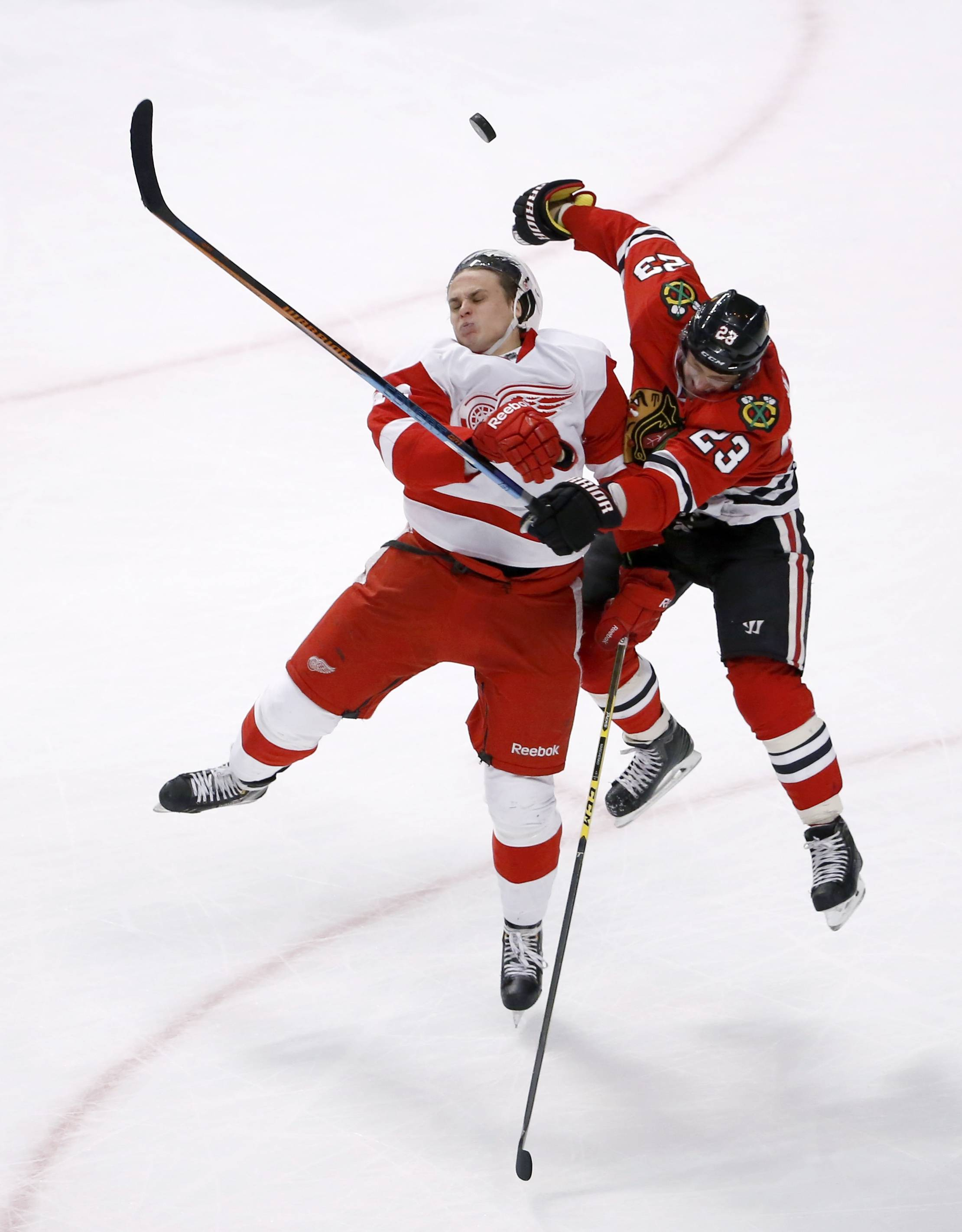 The Blackhawks' Kris Versteeg and the Red Wings' Alexei Marchenko collide going for the puck during overtime Wednesday at the United Center. The Hawks lost 3-2 in a shootout.