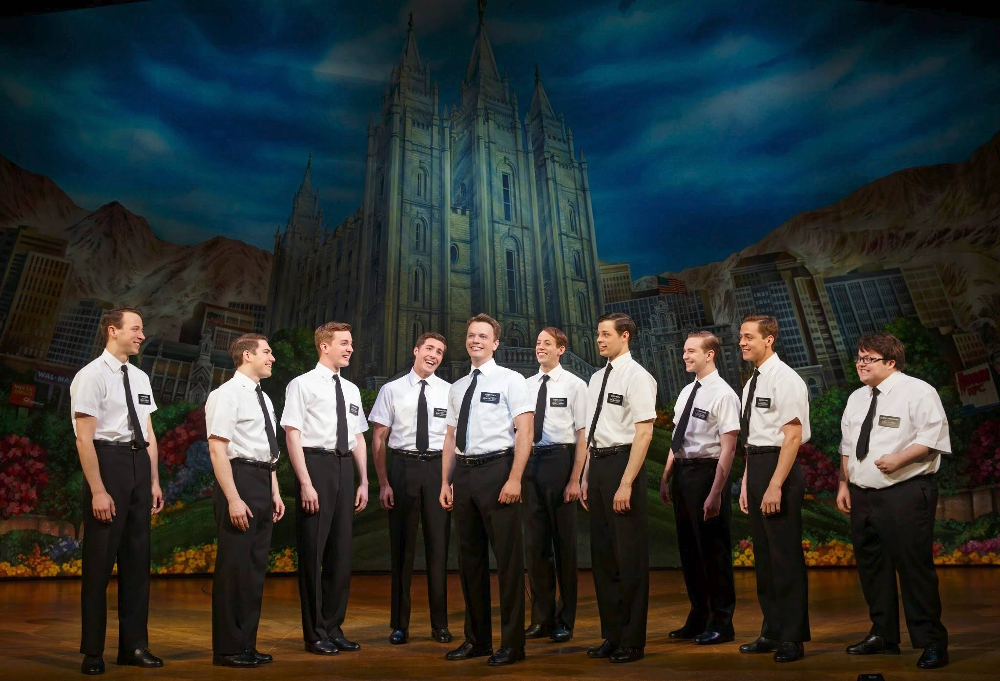 "Elder Price (David Larsen), center, and Elder Cunningham (Cody Jamison Strand), far right, are part of a group of newly trained missionaries for the Church of Jesus Christ of Latter-day Saints awaiting to find out where they will be serving their missions in the second national tour of ""The Book of Mormon."""