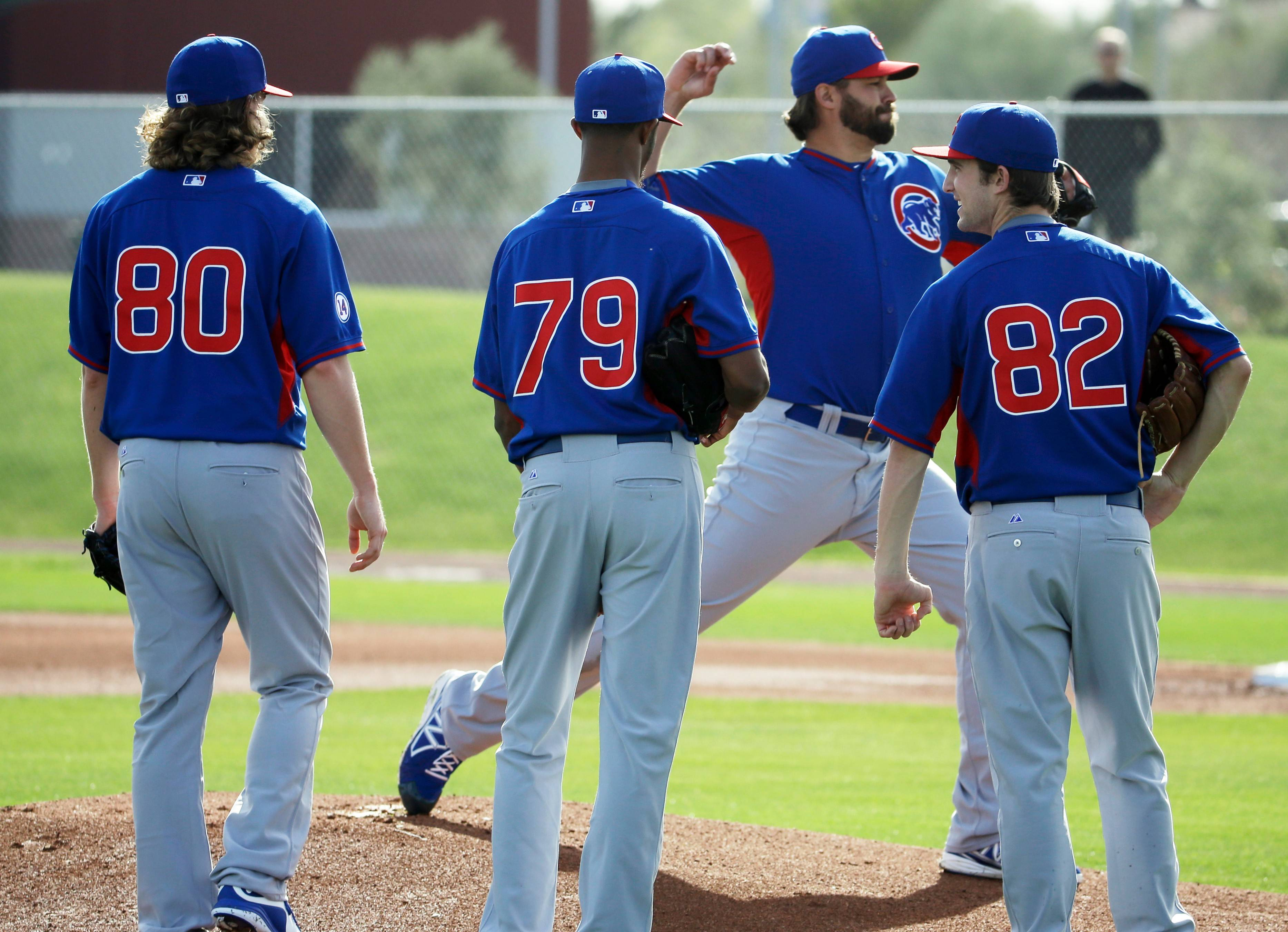 Teammates watch as Chicago Cubs Anthony Carter simulates a throw from the mound during a spring training baseball workout Saturday, Feb. 21, 2015, in Mesa, Ariz.