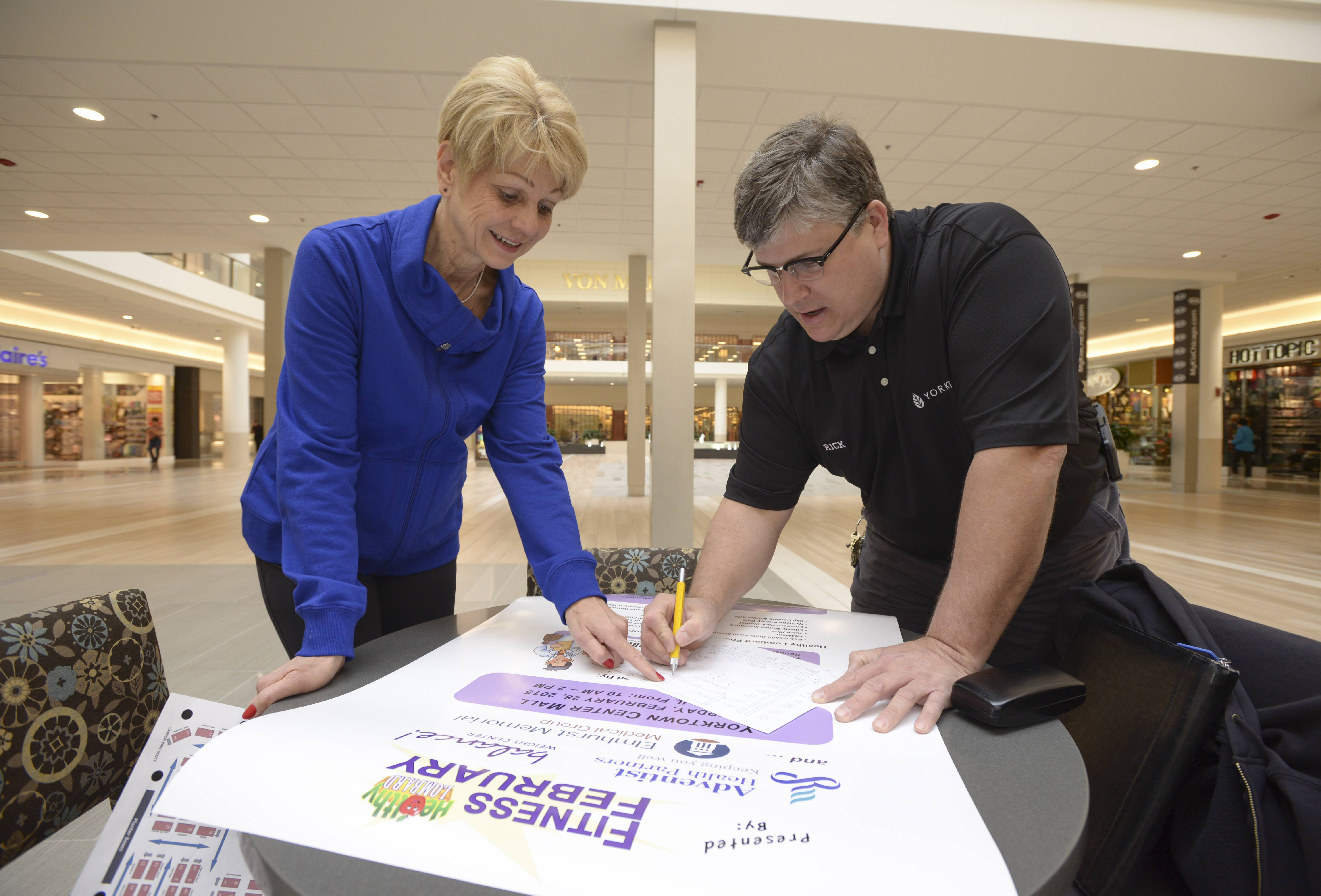 Jay Wojcik, the volunteer director of Healthy Lombard, works with Yorktown Center Chief Engineer Rick Fugger on the setup of the February Fitness Fair on Feb. 28.