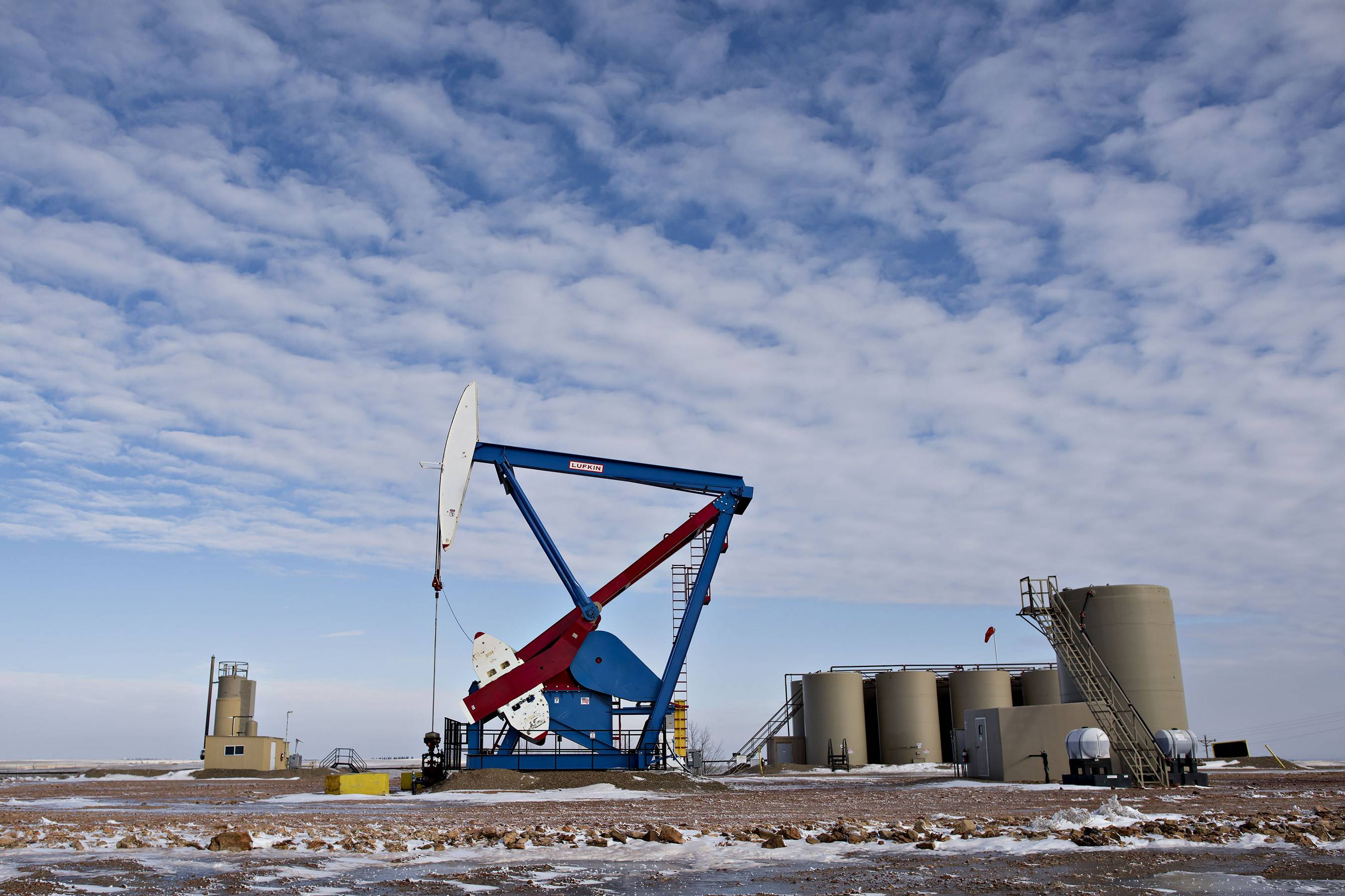 A pumpjack stands near storage containers on the site of an oil well outside Williston, North Dakota. A plunge in global energy prices that has put some North Dakota oil rigs in a deep freeze has yet to chill the state's hiring climate. Brent crude, a benchmark for international oils used by many U.S. refineries, fell $1.58 Thursday to close at $60.05 in London. In other futures trading on the NYMEX, wholesale gasoline fell 1.1 cents to close at $1.708 a gallon.