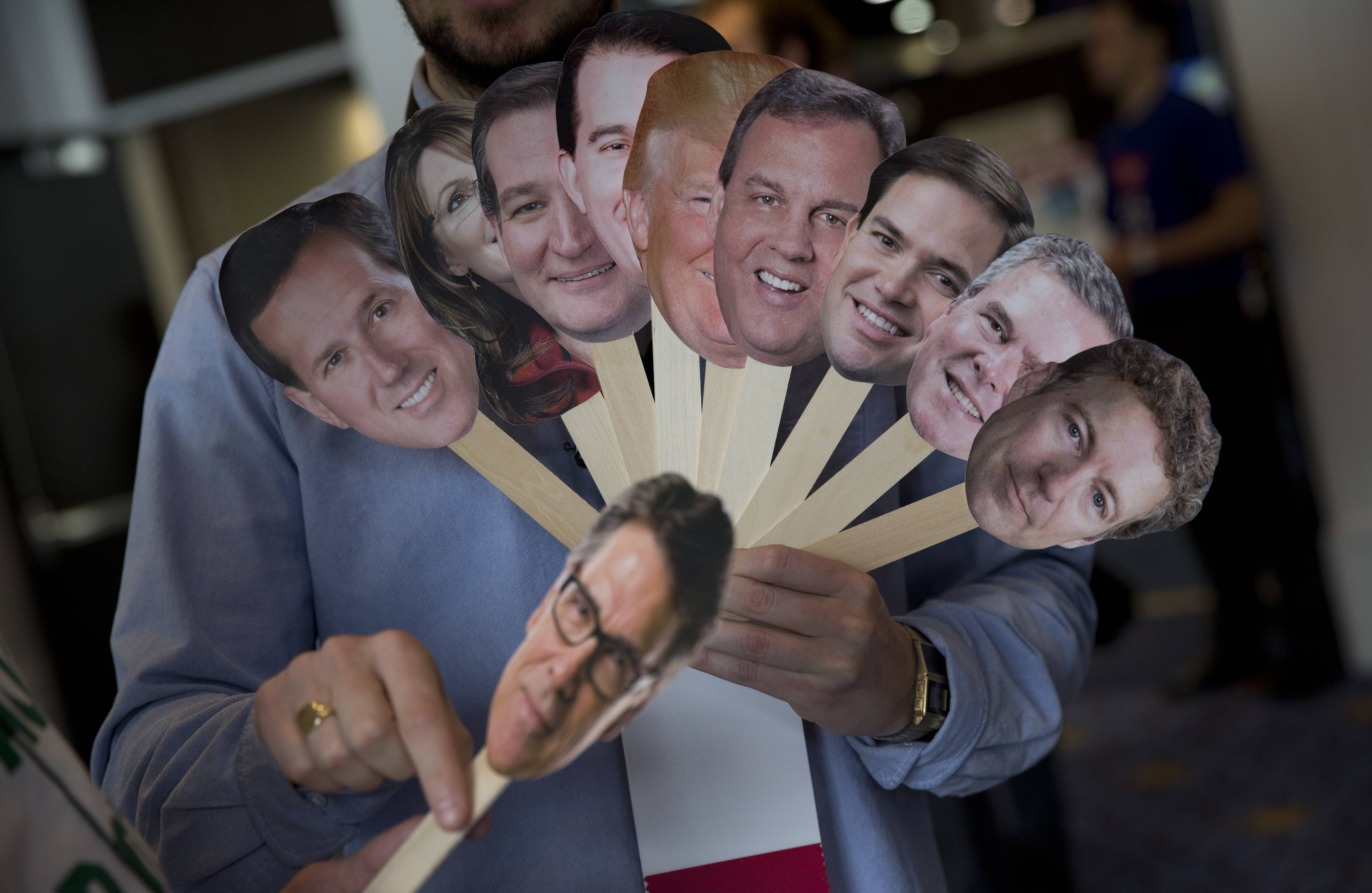 "Adam Gabbatt of The Guardian newspaper holds images of possible Republican candidates, from left, former Pennsylvania Sen. Rick Santorum, former Alaska Gov. Sarah Palin, Sen. Ted Cruz, R-Texas, Wisconsin Gov. Scott Walker, Donald Trump, New Jersey Gov. Chris Christie, Sen. Marco Rubio, R-Fla., former Florida Gov. Jeb Bush, Sen. Rand Paul, R-Ky., and, former Texas Gov. Rick Perry, below, as he interviews Howard ""Cowboy"" Woodward during the Conservative Political Action Conference (CPAC) in National Harbor, Md., Thursday, Feb. 26, 2015."
