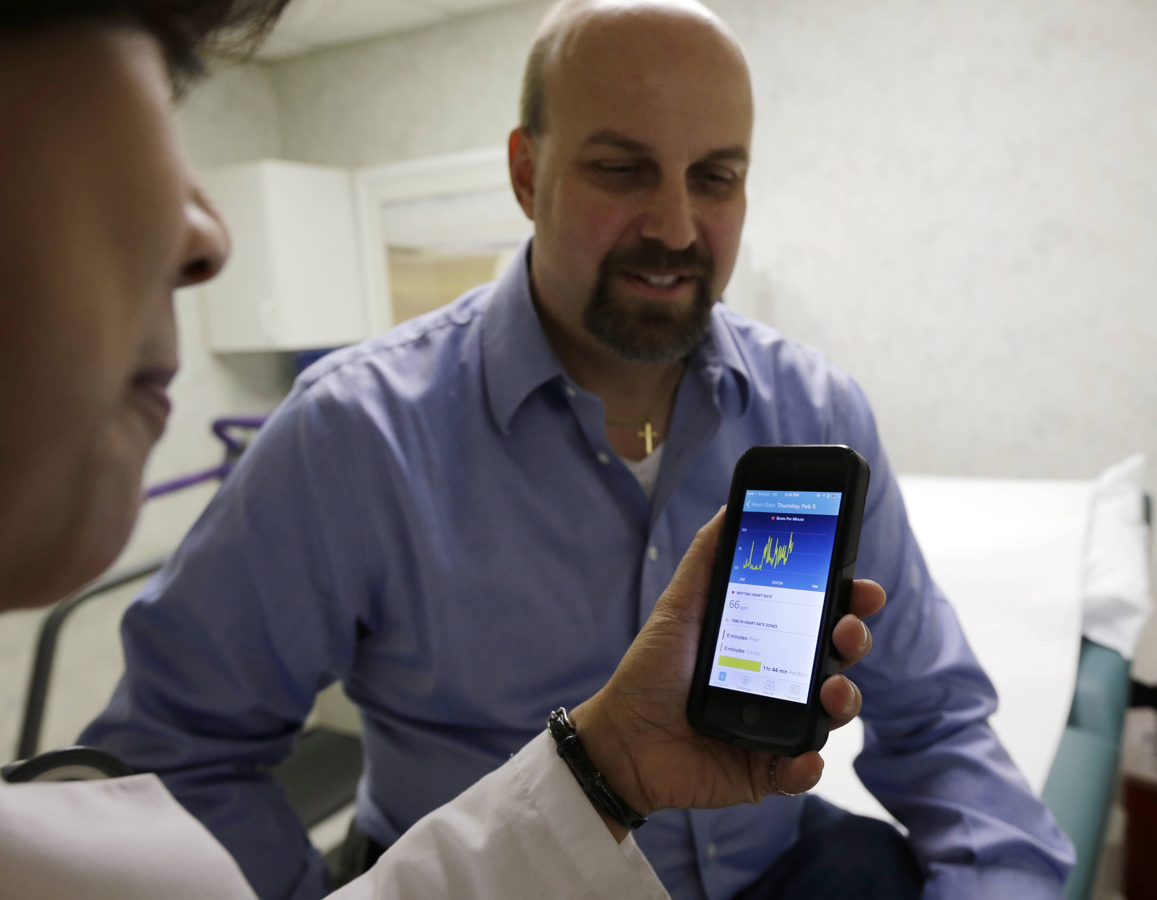 Hackensack University Medical Center cardiologist Dr. Sarah Timmapuri, left, looks at data on a smartphone synchronized to a new Fitbit Surge worn by patient Gary Wilhelm, 51, during an examination in Hackensack, N.J. Wilhelm, who works at Hackensack University Medical Center on payroll and finance technology, joined Hackensack's app test after he suffered a heart attack in October.