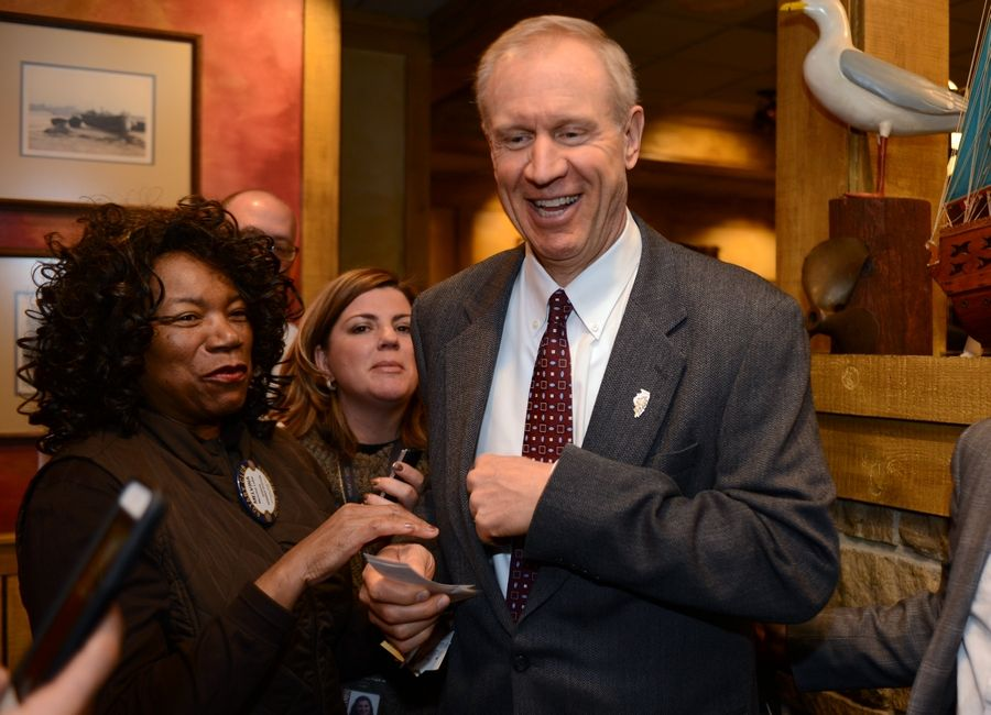 Gov. Bruce Rauner smiles after buying two raffle tickets from Mundelein Vernon Hills Rotary Club member Melvina Lube of Mettawa. Rauner spoke during the group's weekly meeting Monday in Mundelein.