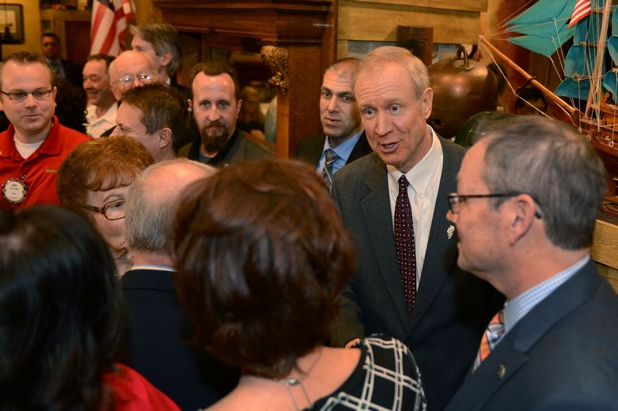 Gov. Bruce Rauner, second from right, visits with Mundelein Vernon Hills Rotary Club members after his speech Monday at the Dover Straits restaurant in Mundelein.