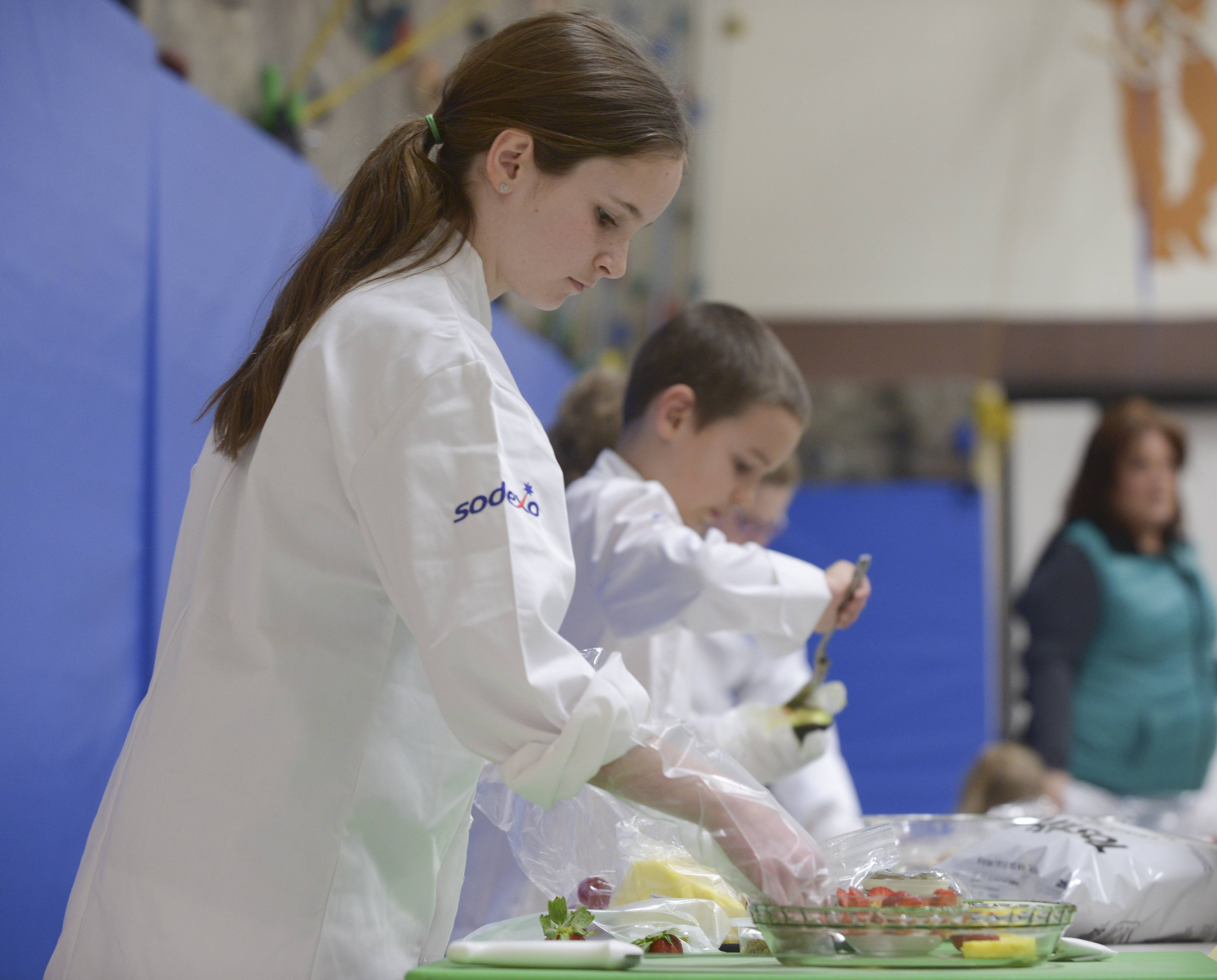 Scott Elementary fifth-grader Nora Johnson-Guy, 11 of Naperville, creates Fruity Faces on Wednesday during the Future Chefs Challenge sponsored by Sodexo.