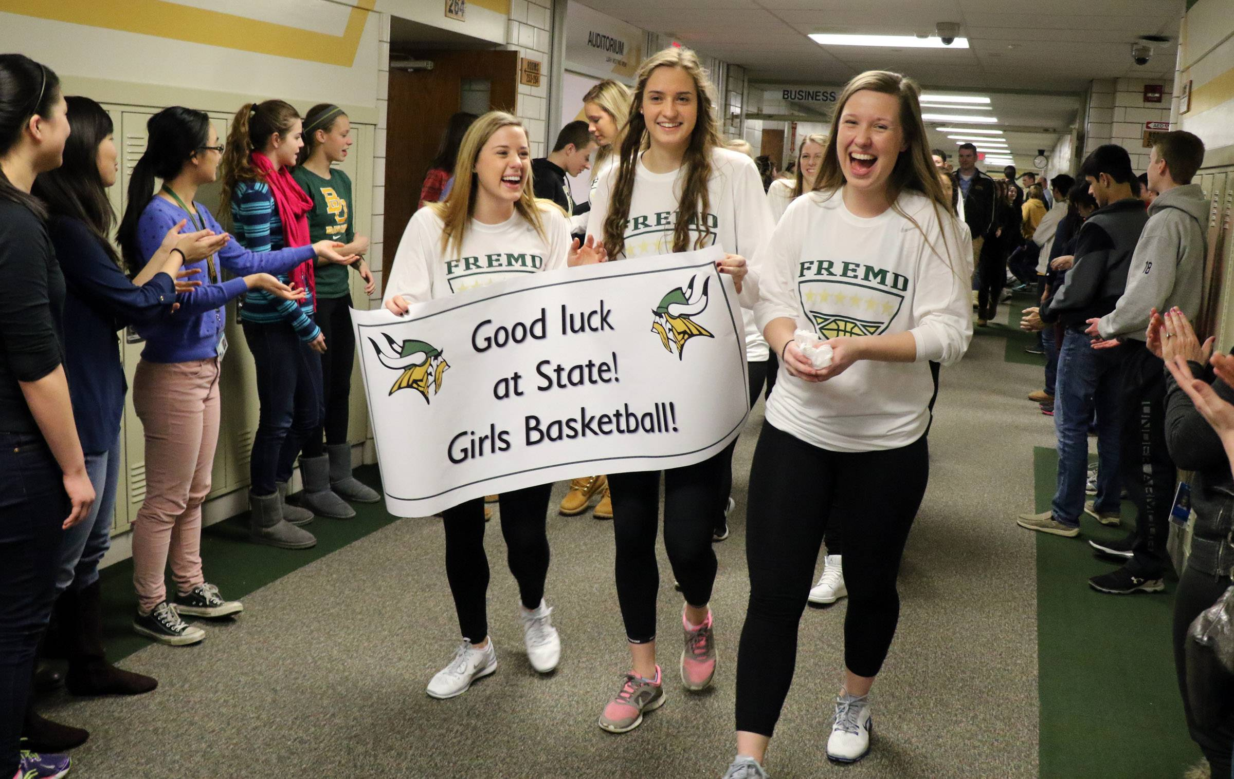 Fremd High School girls' basketball team members, including co-captains Emily Bieda, left, and Haley Gorecki, carrying the sign, march through the school's hallways Wednesday as the team got a big send-off to the state tournament in Palatine. The girls depart on Thursday.