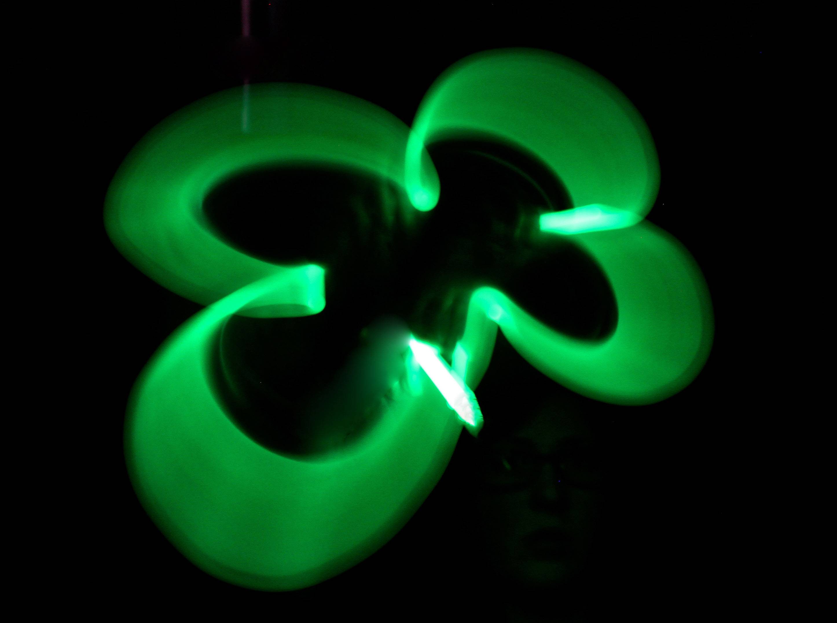 I purchased some glow sticks on a recent shopping trip. I waited until sundown and then turned off the lights and made my room completely dark. I opened up a green glow stick and took long exposure photos with the camera resting on my desk. I moved the stick in the shape of a four-leaf clover and ended the motion at the stem. The photo is a 5 second exposure.