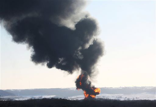 Smoke and flames erupt from the scene of a train derailment Thursday, March 5, 2015, near Galena, Ill. A BNSF Railway freight train loaded with crude oil derailed around 1:20 p.m. in a rural area where the Galena River meets the Mississippi, said Jo Daviess County Sheriff's Sgt. Mike Moser.