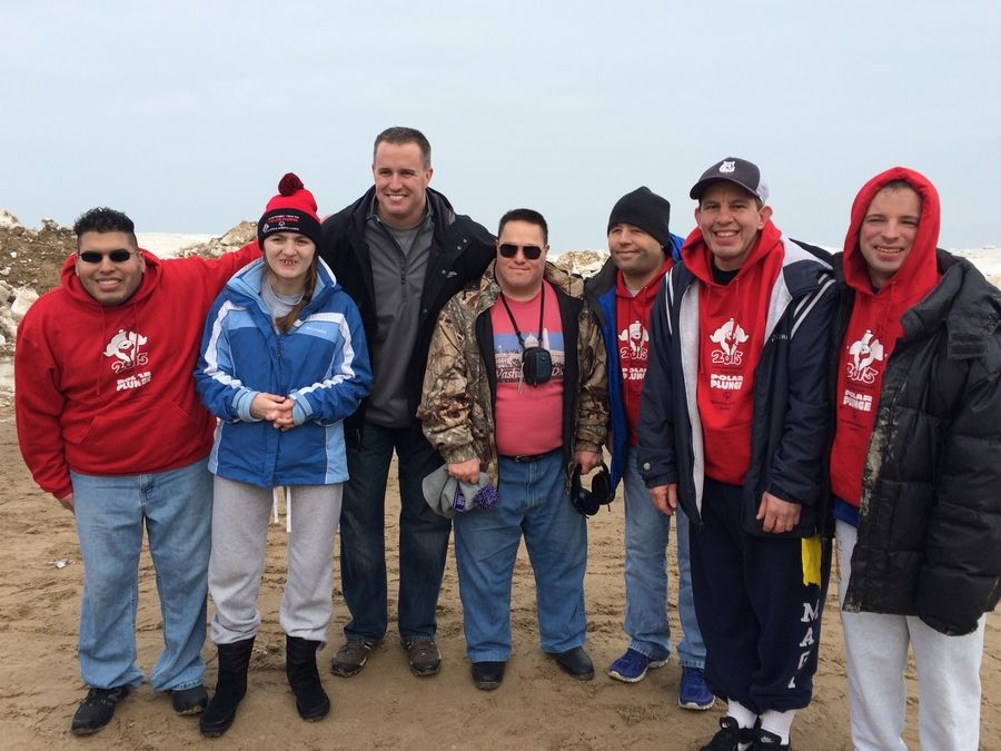 Northwestern Wildcats football coach Pat Fitzgerald, third from left, greets the chilled NEDSRA plunging team after the Special Olympics Polar Plunge in Evanston in mid-February.