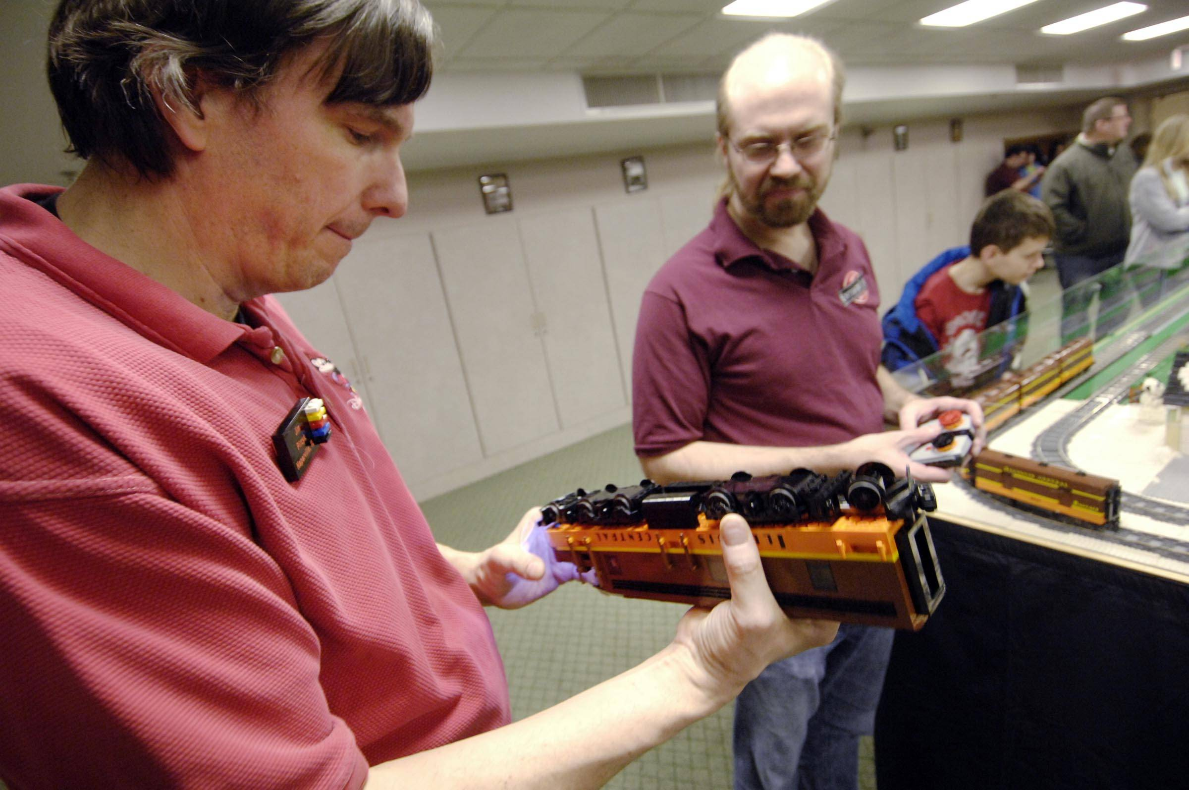 Club member Jim Pirzyk of Naperville holds a LEGO train while Matt De Lanoy of Woodridge holds the LEGO remote that drives the train on Sunday at an exhibit by the Northern Illinois LEGO Train Club at the Geneva Public Library.
