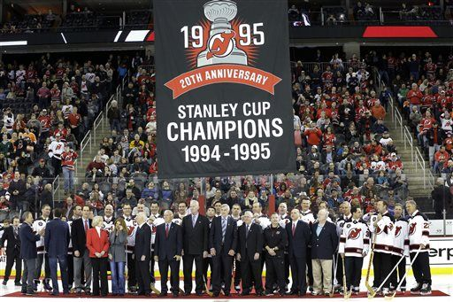 667b32f5f A banner is raised over the New Jersey Devils 1995 Stanley Cup winning team  as they