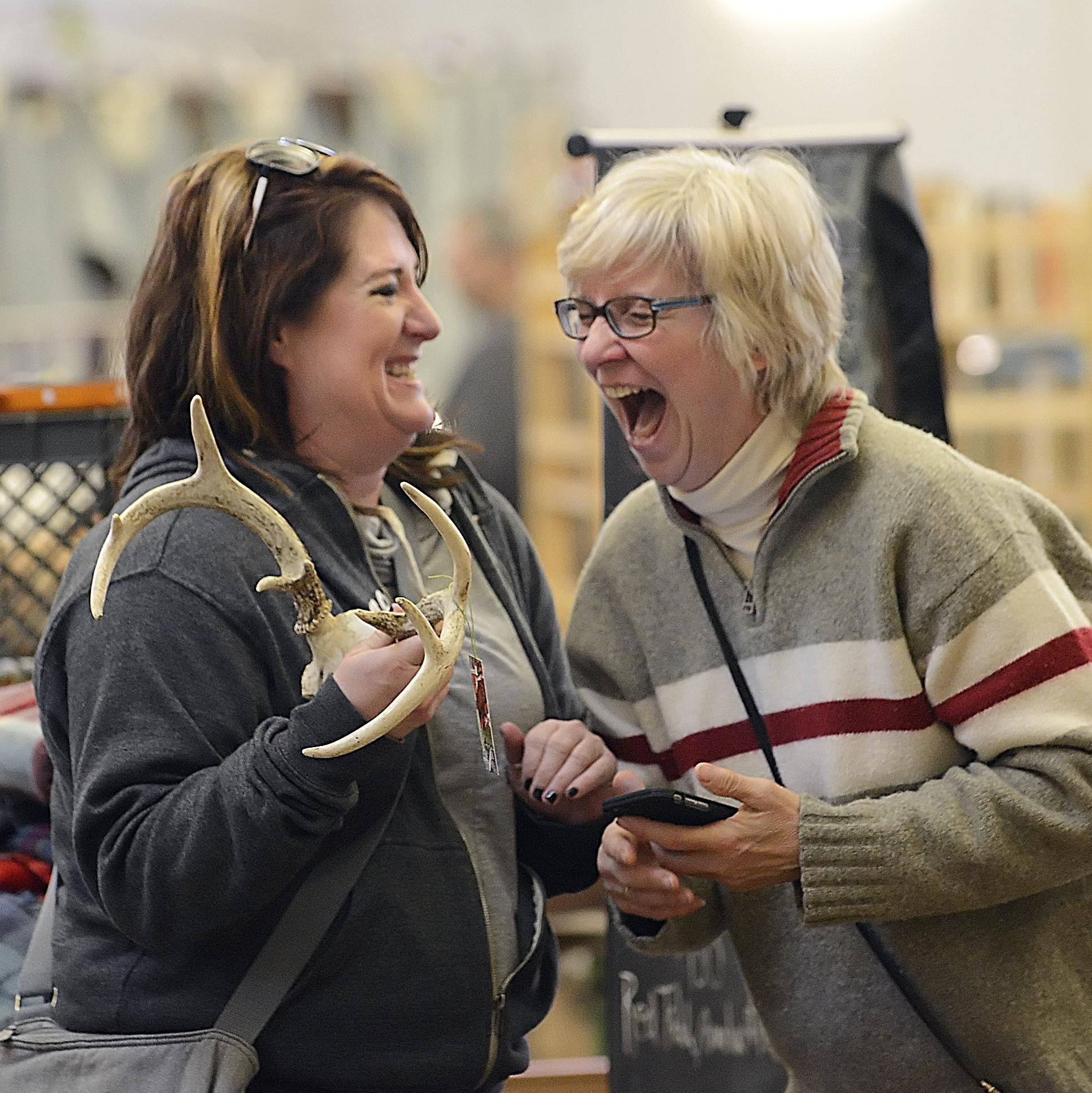 Lisa Michaels, left, of South Elgin, laughs with Kathy Filipiak, of St. Charles, while they discuss the price of deer antlers at the first Kane County Flea Market of 2015 at the fairgrounds in St. Charles. Filipiak was manning a booth for This2That for a friend.