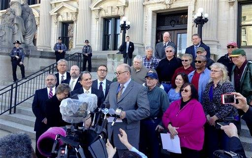 Illinois AFL-CIO President Michael Carrigan is joined by state workers and retirees outside the Illinois Supreme Court in Springfield, Ill., Wednesday, March 11, 2015, as he addresses the media following oral arguments in a lawsuit over a state pension overhaul. Workers and retirees, who sued over the law, say they shouldn't be punished because lawmakers for years failed to contribute the state's share to the pension funds.