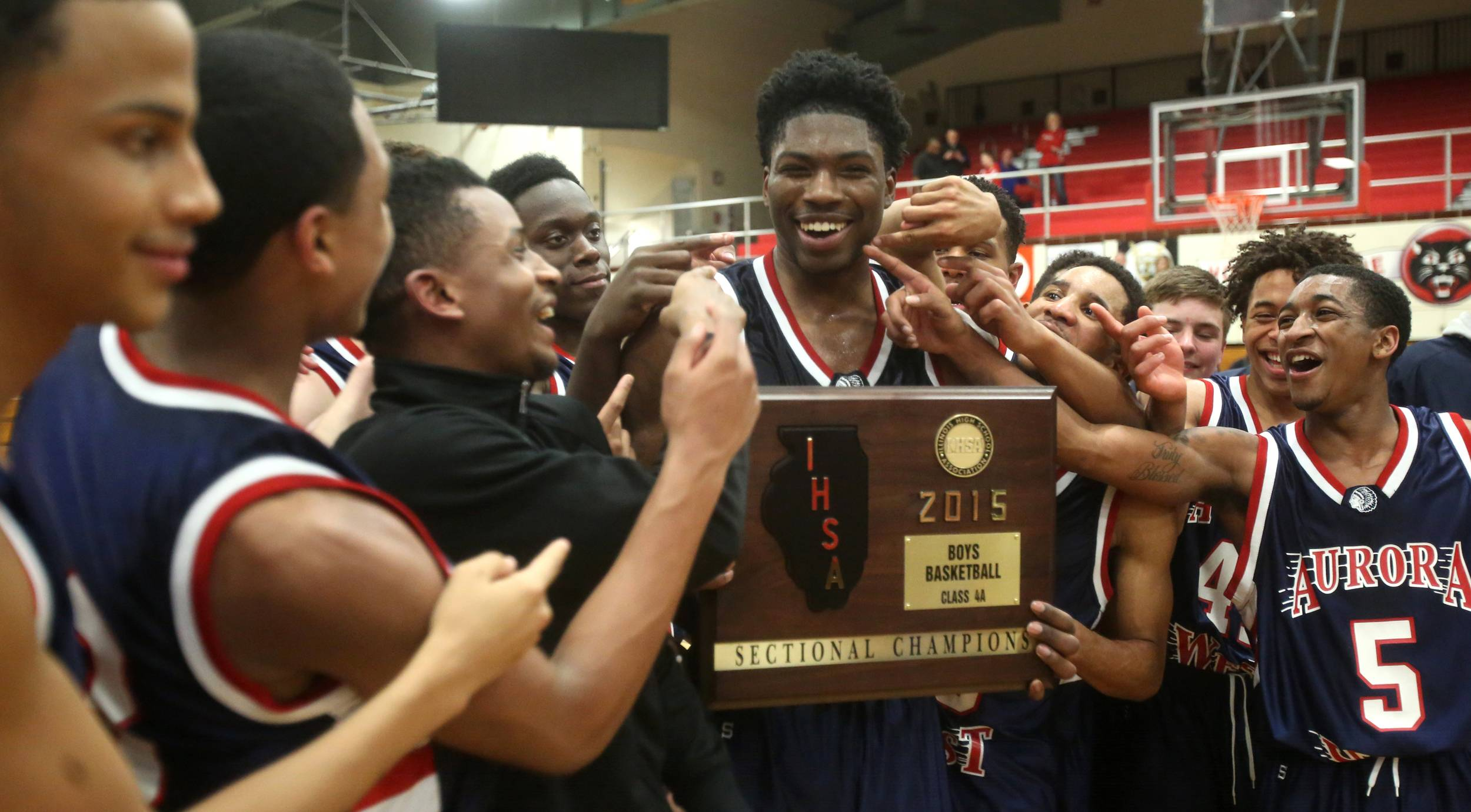 All fingers point to Roland Griffin, who celebrates with his teammates the Class 4A East Aurora boys basketball sectional championship. Griffin scored 31 points.