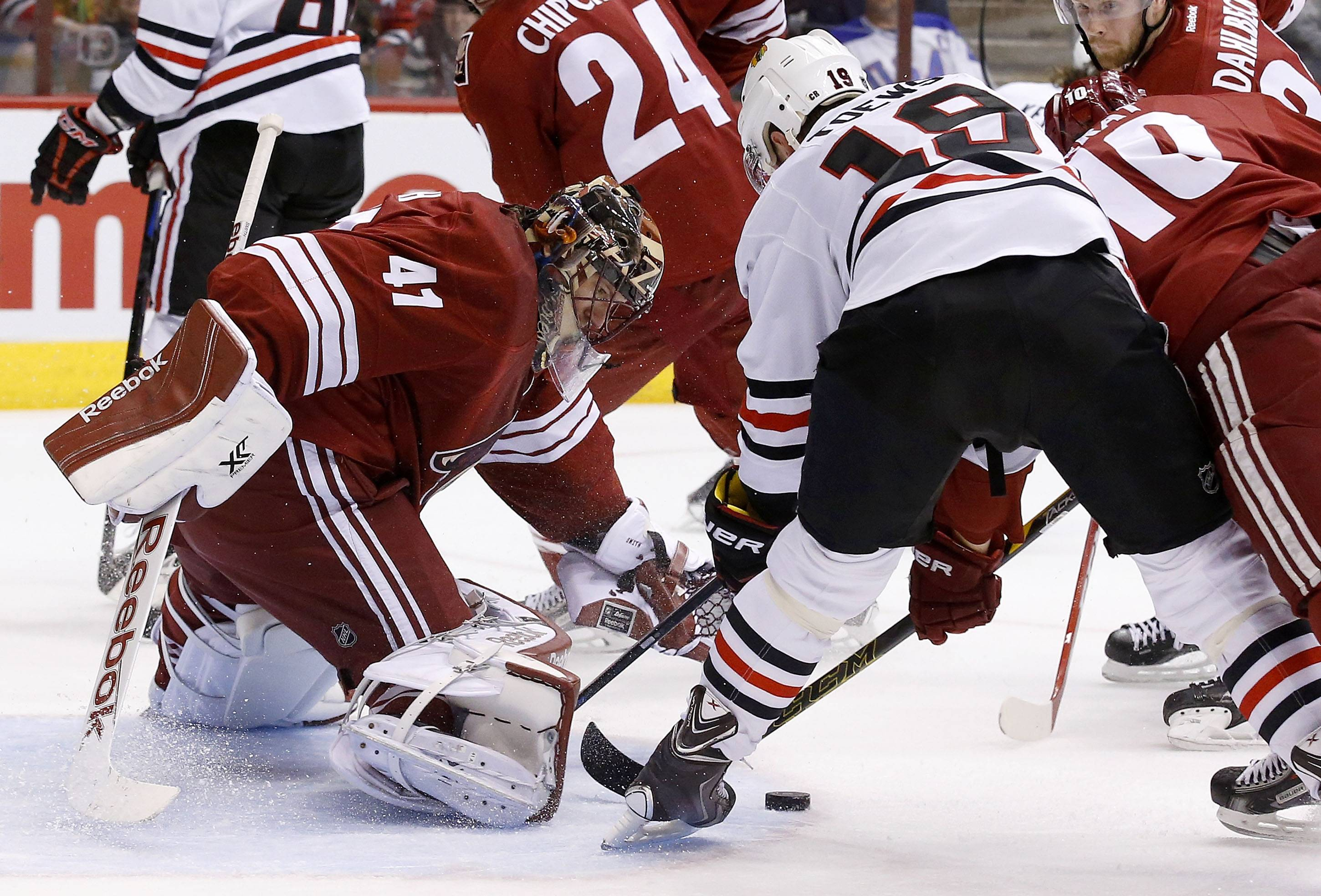The Blackhawks' Jonathan Toews (19) tries to get a shot off in front of Arizona Coyotes' Mike Smith (41) as Coyotes' Martin Erat (10) defends during the first period of the game Thursday in Glendale, Ariz.