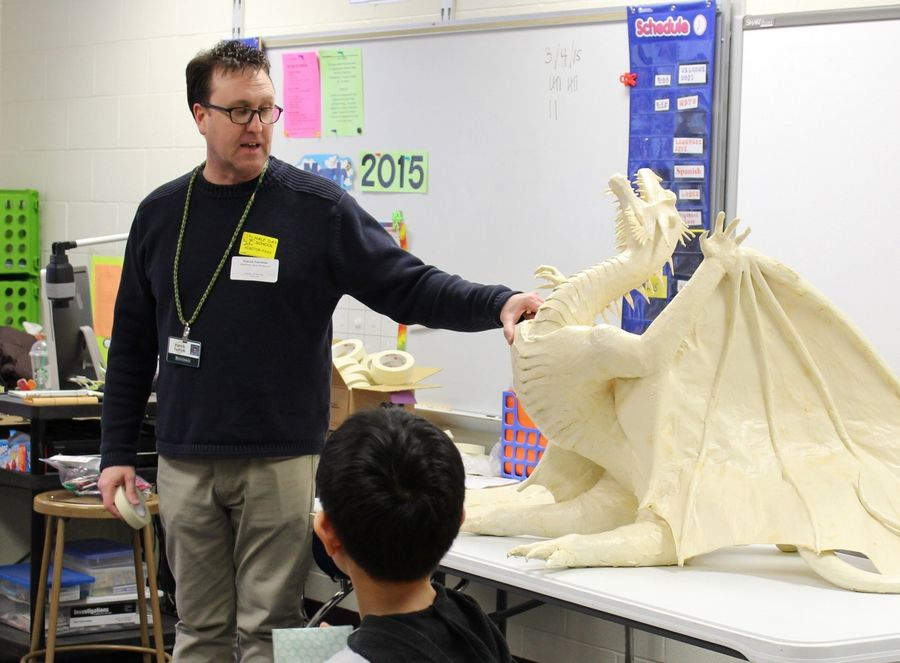 Patrick Fairchild, Stevenson High School visual arts teacher, describes to students at Half Day School what's involved in designing a masking tape sculpture, like this elaborate dragon he created more than five years ago. The Lincolnshire school recently held an Explore the Arts Day.