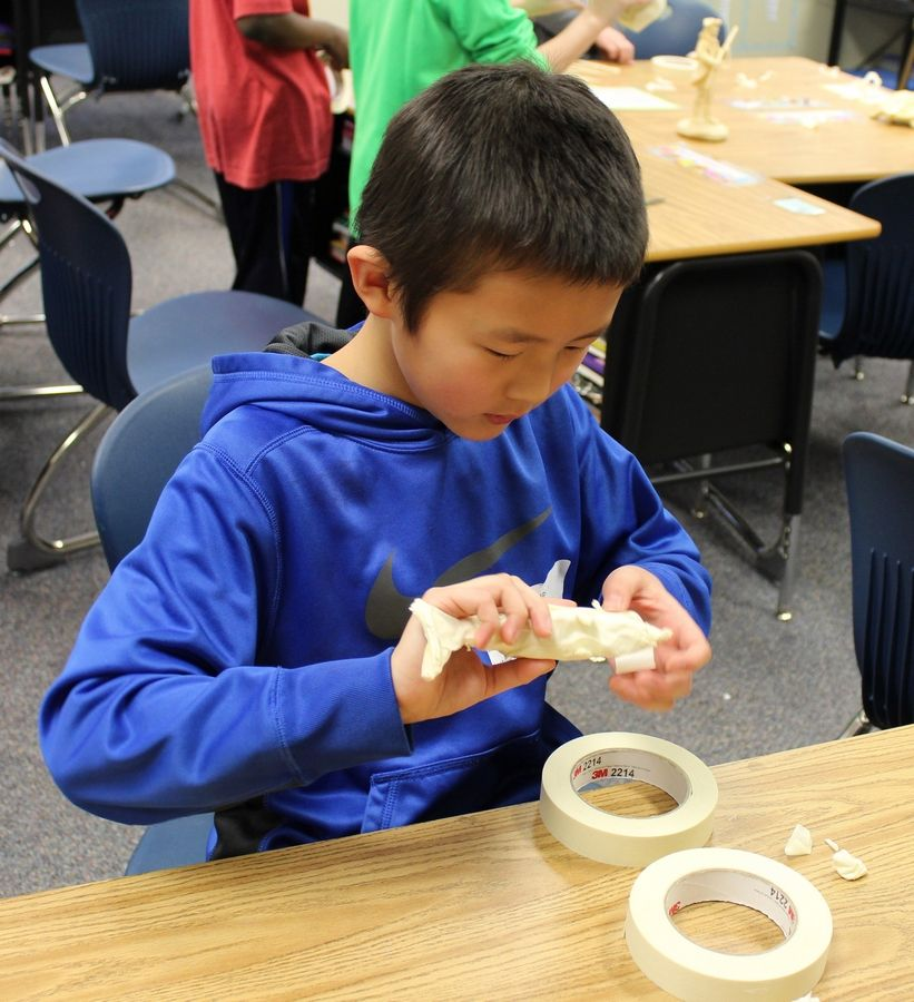 A student from Half Day School works to perfect the dolphin sculpture he created from masking tape during Explore the Arts Day.