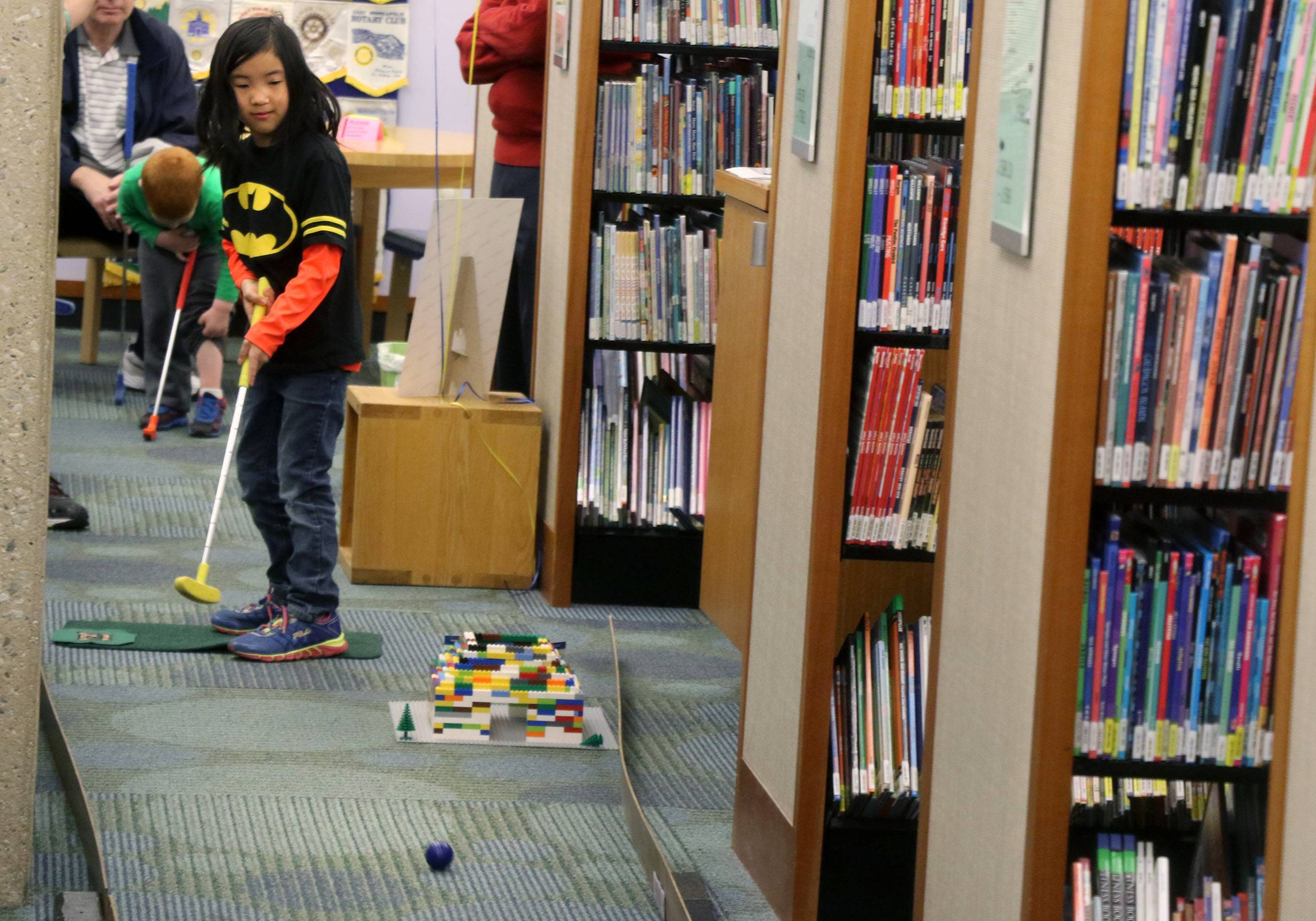 Jenna Fasick, 6, of Mount Prospect, plays hole 12 of an 18-hole miniature golf course at the Mount Prospect Library as part of a fundraiser in Mount Prospect.