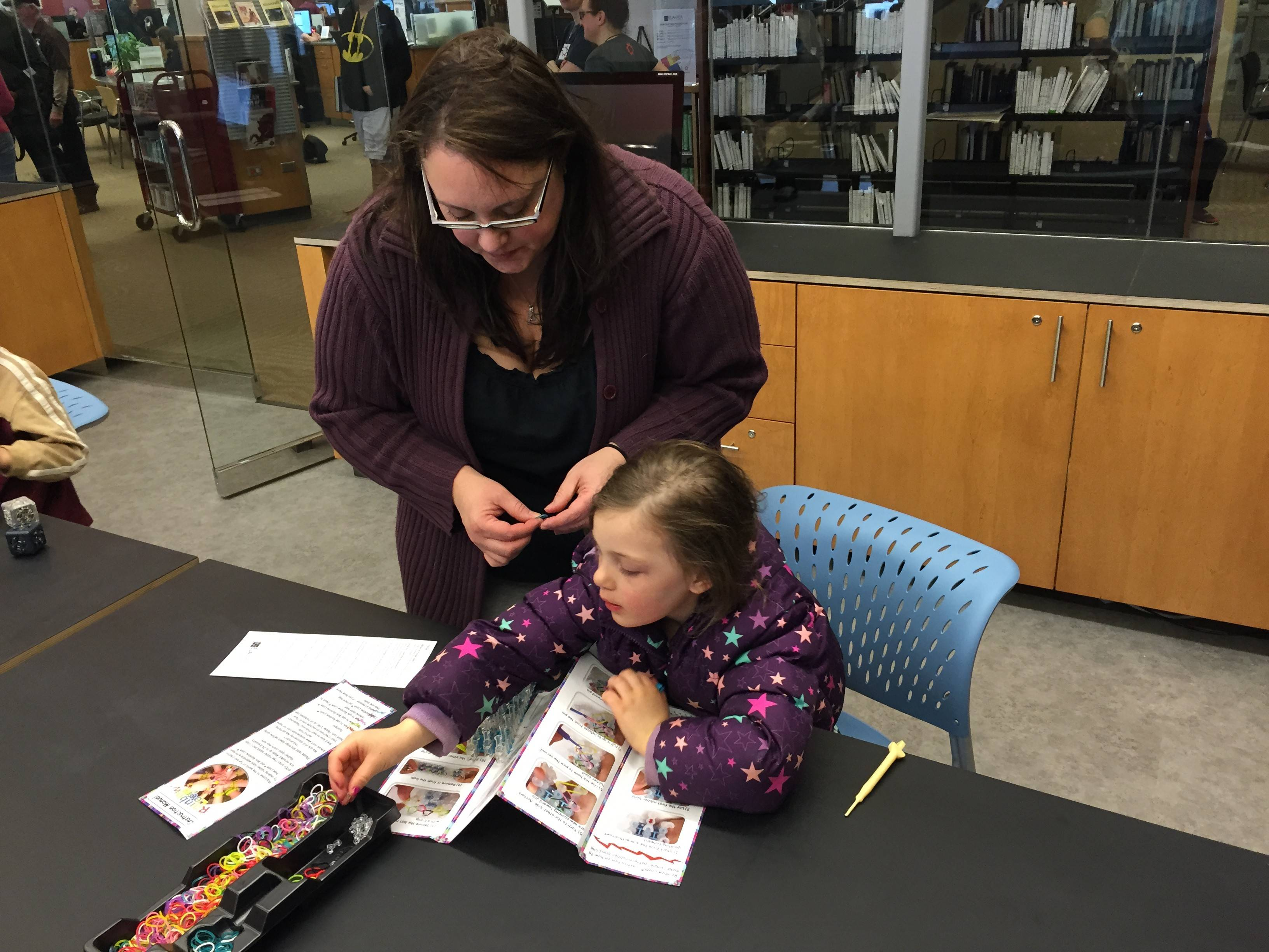 Kim Bettasso and her 3-year-old daughter Isobel work with Rainbow Looms on opening day of the Ela Area Public Library's new makerspace, called Forge.