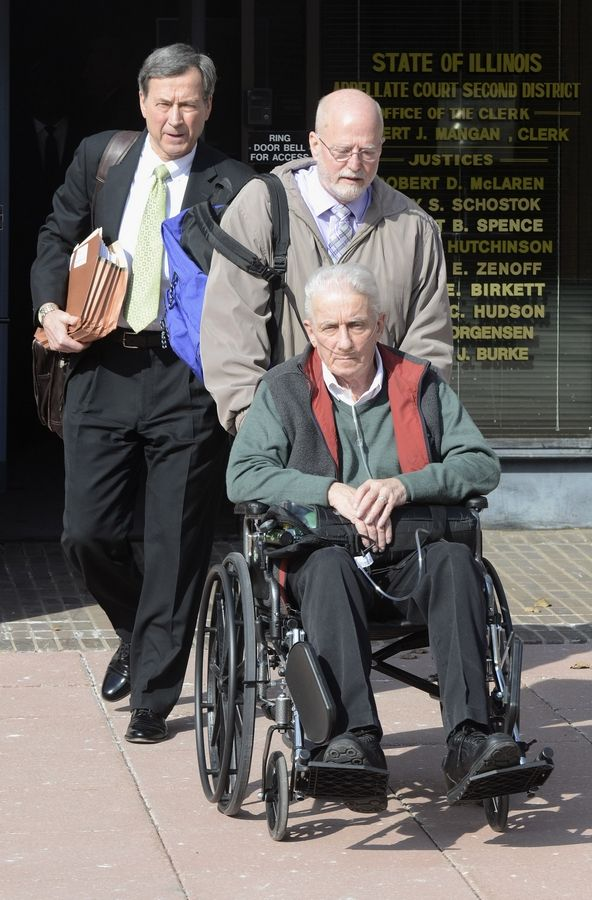 Former state Rep. Keith Farnham, in a wheelchair, leaves the 2nd District appellate courthouse in Elgin with his attorney Terry Ekl, far right, after being sentenced to eight years in prison for child pornography.