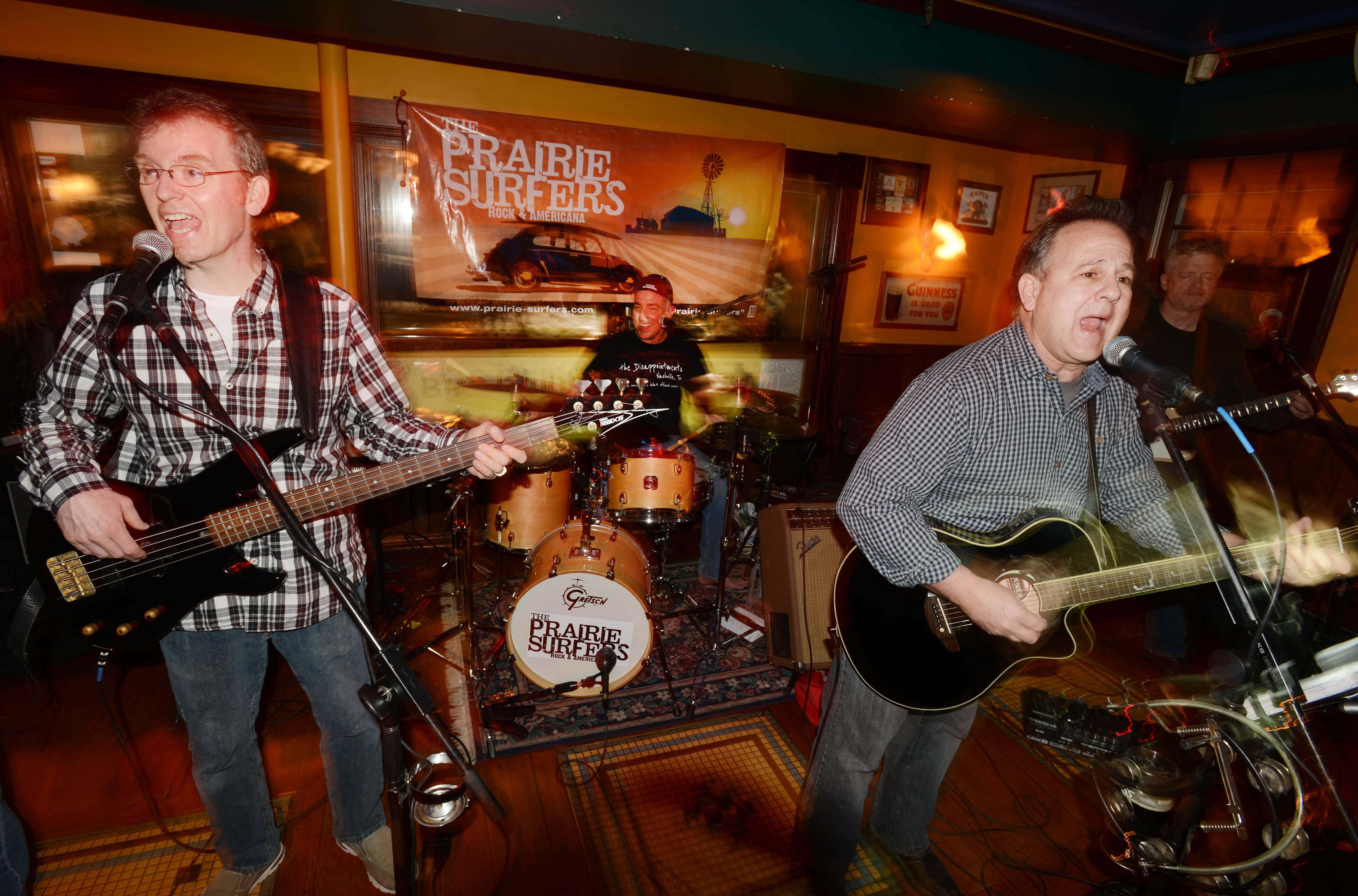 The Prairie Surfers' Glenn Donaldson and KC Holcomb rock the stage at Quigley's Irish Pub in Naperville with drummer Steve Mores of Aurora, who is back with the band after a successful surgery to remove a tumor at his brainstem.